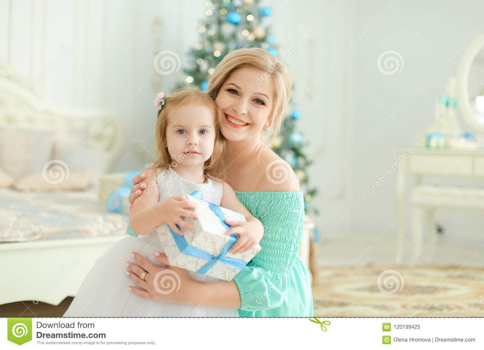 Femme heureuse s asseyant avec la petite fille gardant le présent, arbre de Noël à l arrière-plan