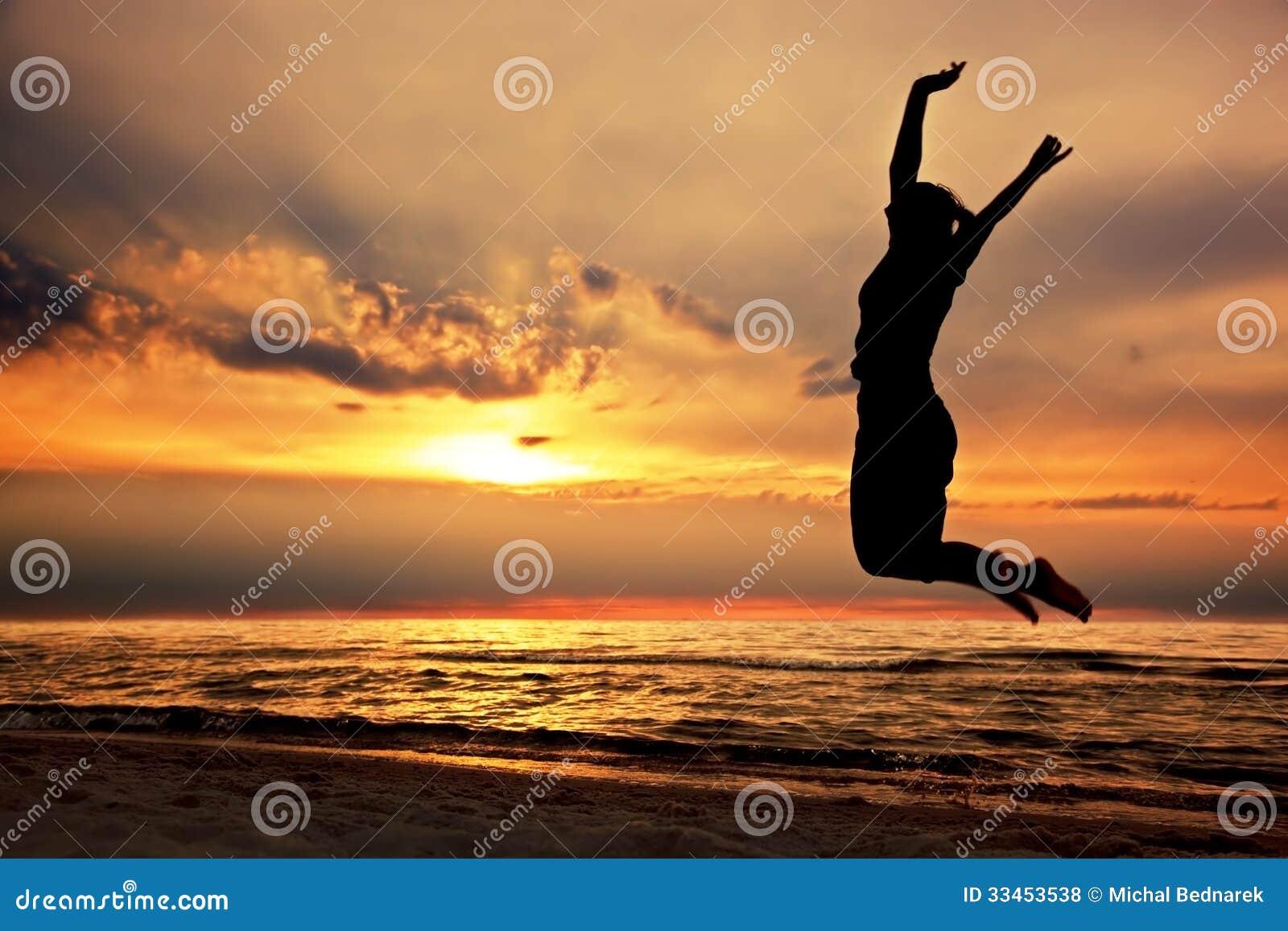 Femme heureuse sautant sur la plage au coucher du soleil