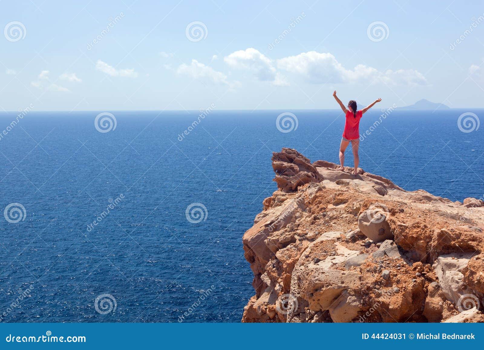 Femme heureuse sur la roche avec des mains  Gagnant, succès, voyage