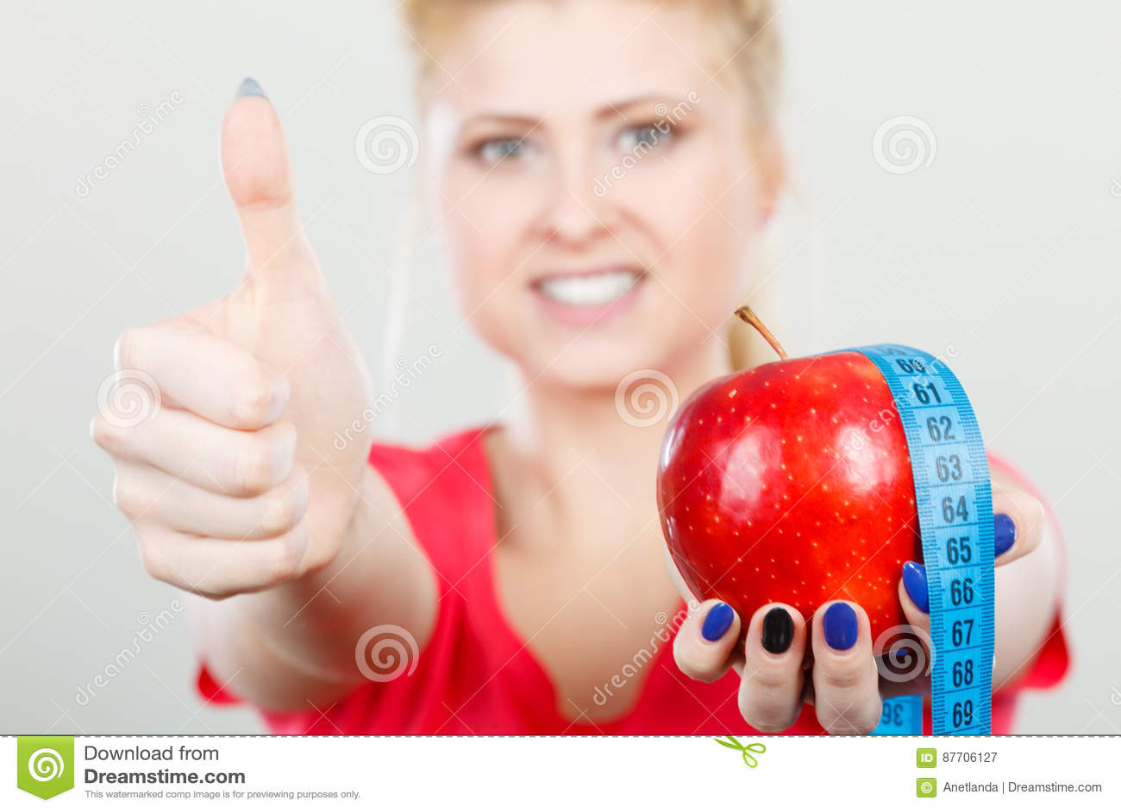 Femme heureuse tenant la pomme et mesurant la bande