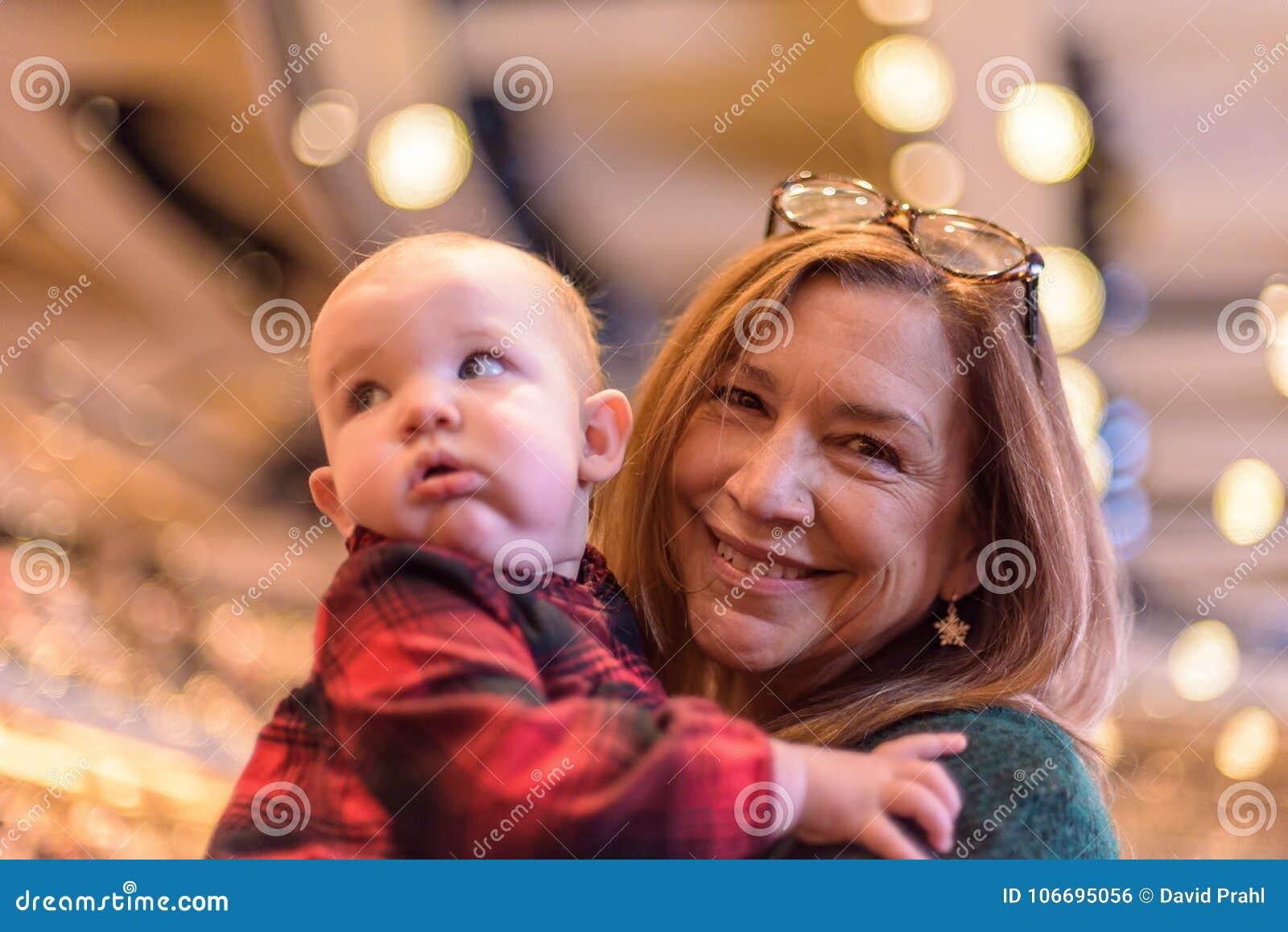 Femme heureuse tenant le bébé dans l église le réveillon de Noël