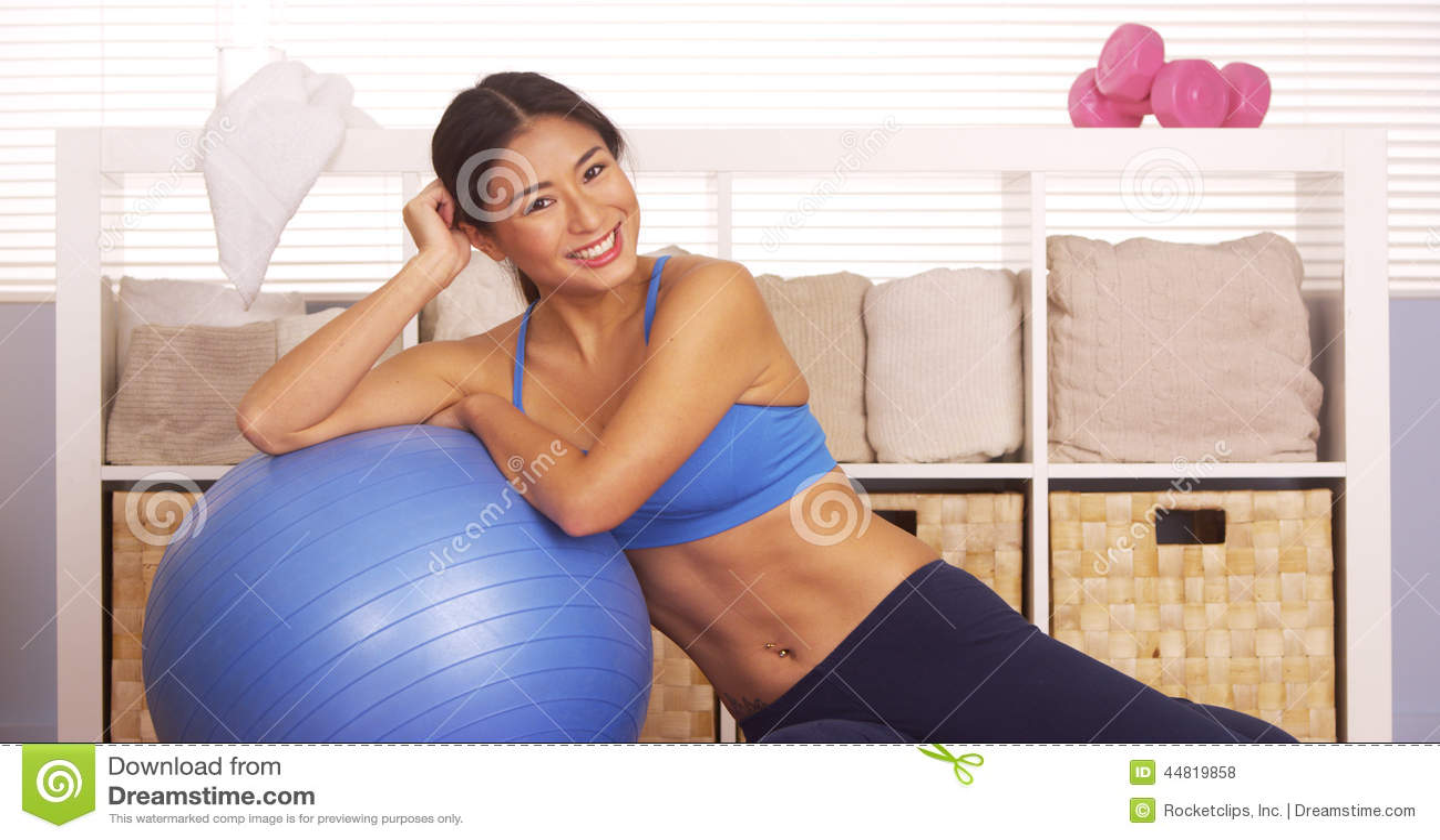 Femme japonaise de sourire se reposant sur la boule de séance d entraînement