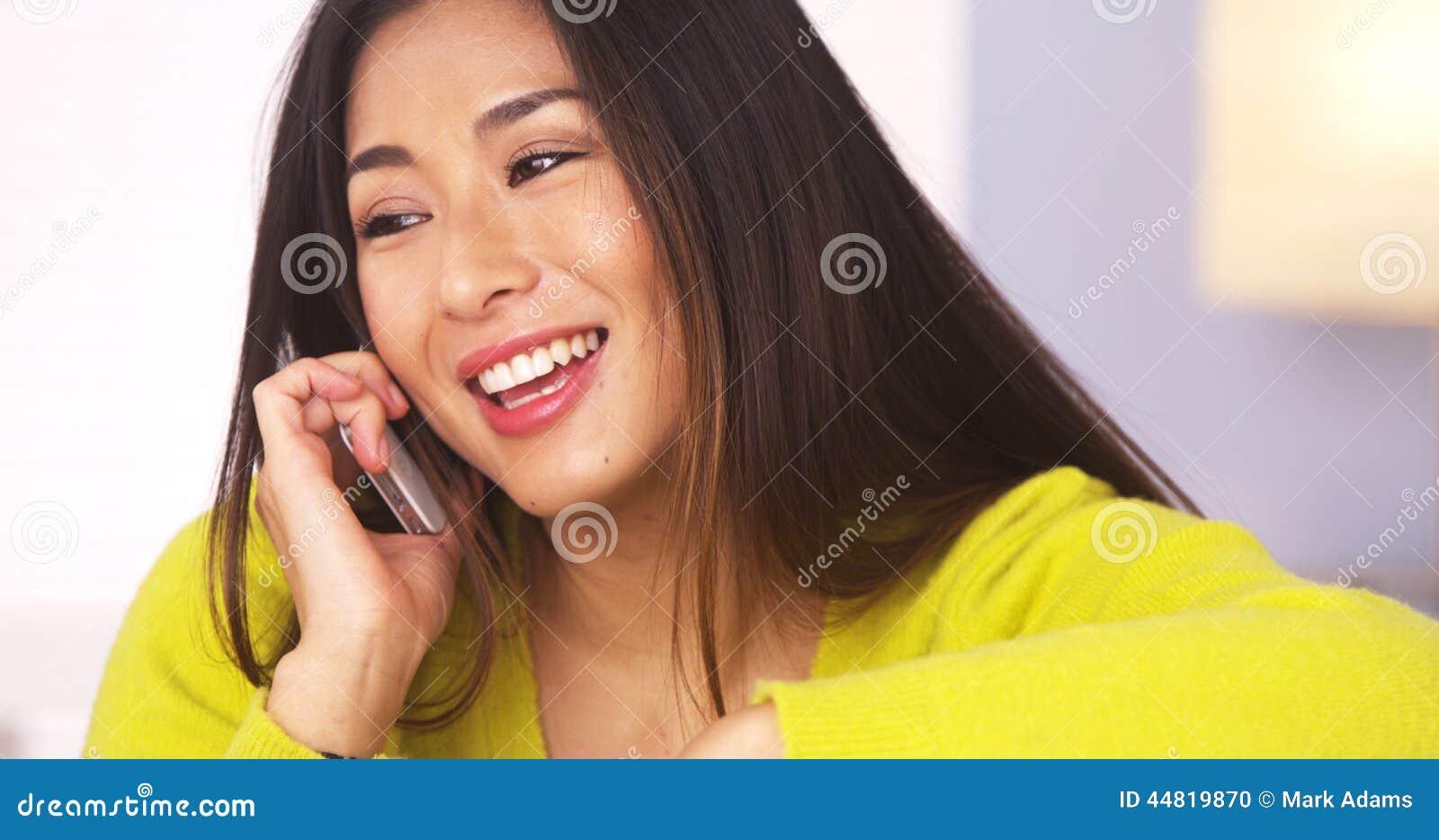 Femme japonaise heureuse parlant sur le smartphone
