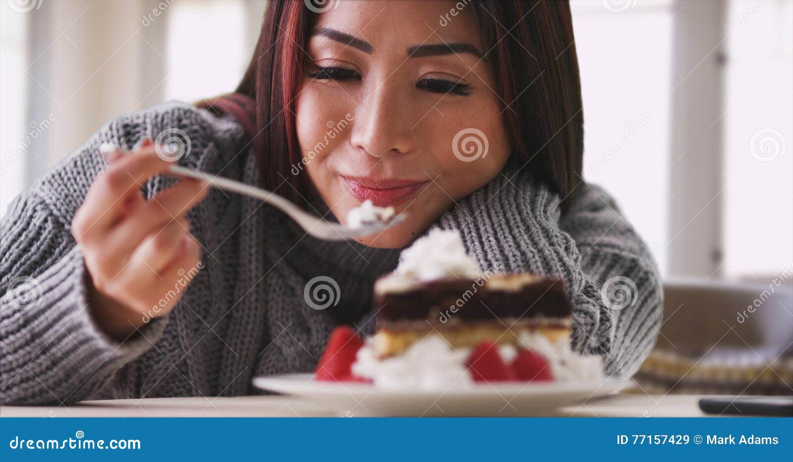 Femme japonaise mangeant le gâteau à la maison