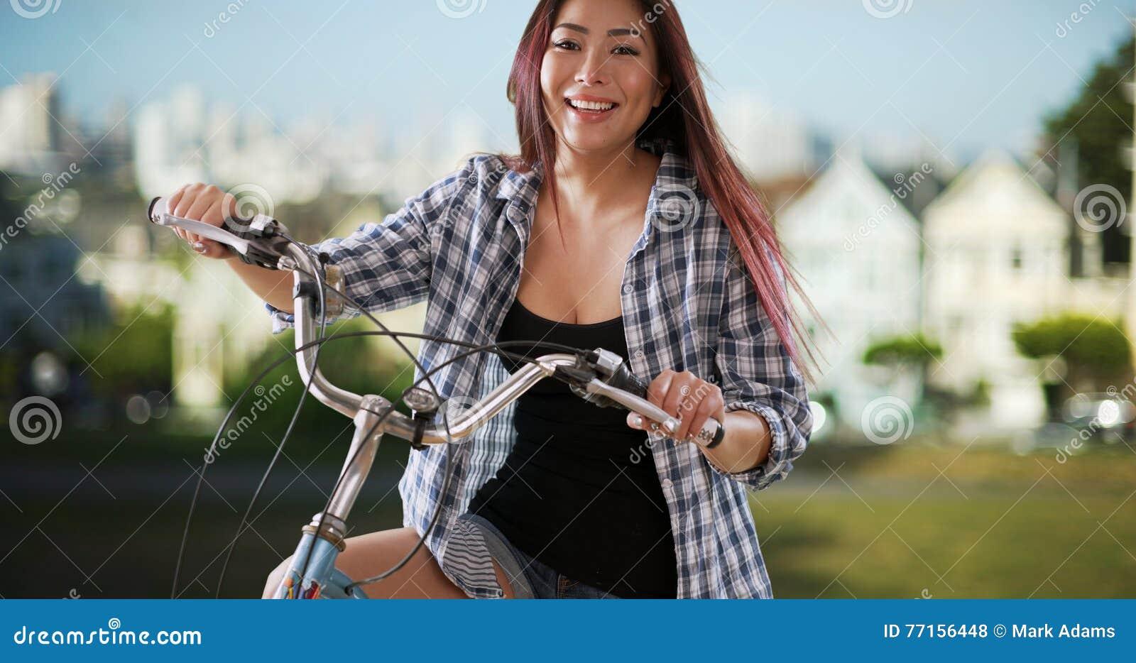 Femme japonaise souriant avec son vélo au parc