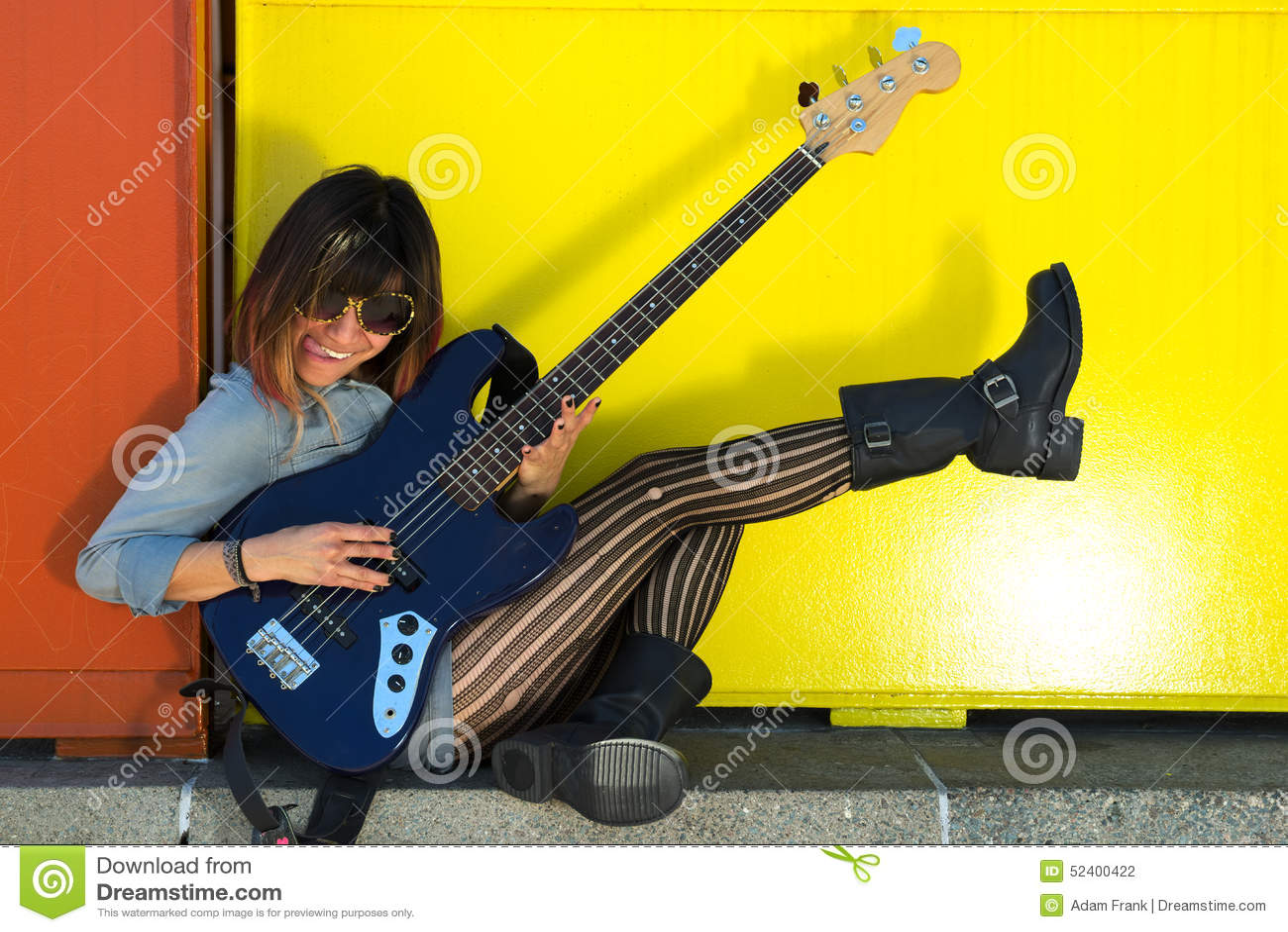 femme jouant la guitare bleue riant et donnant un coup de pied la jambe photo stock image. Black Bedroom Furniture Sets. Home Design Ideas