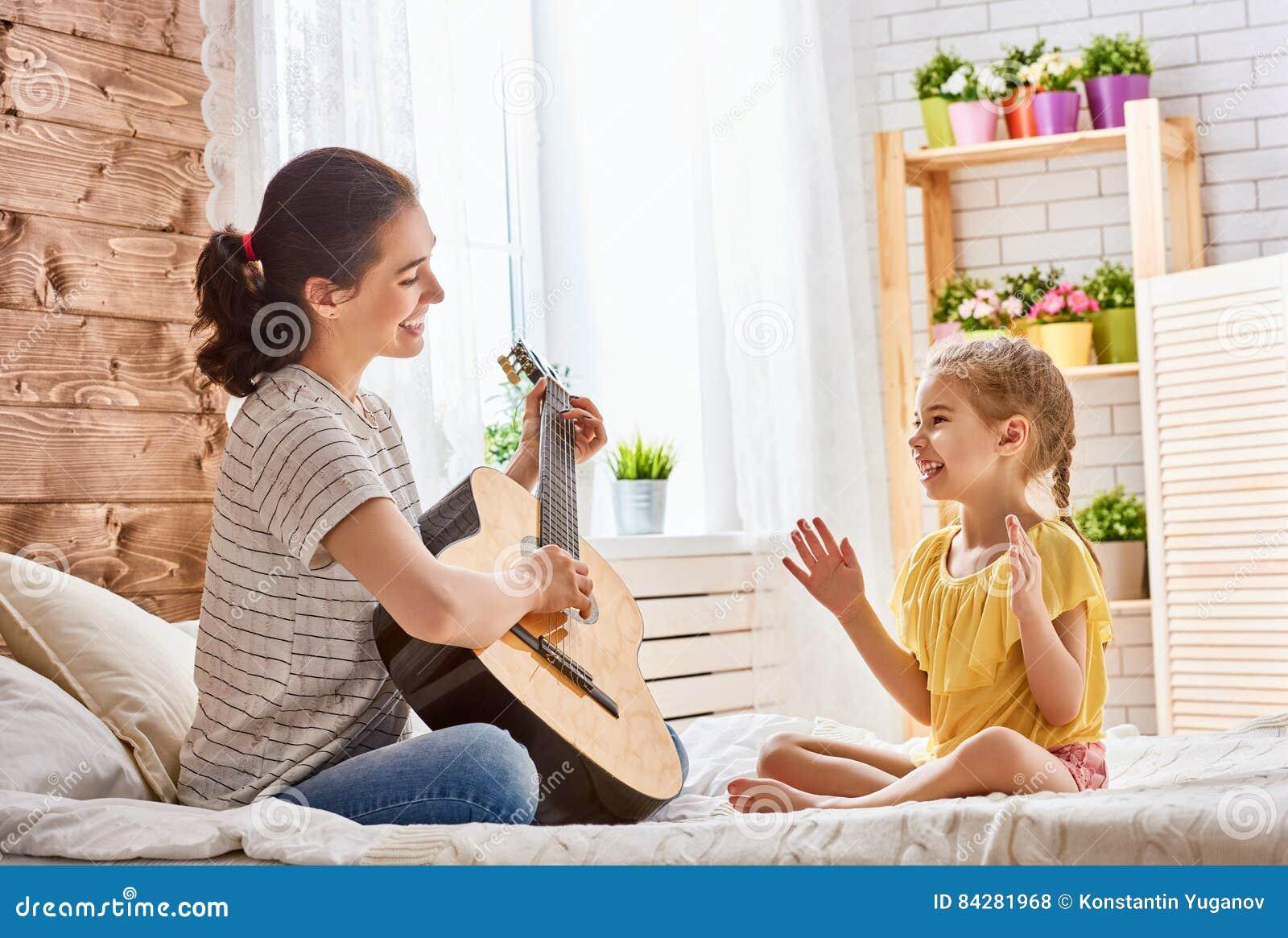 Femme jouant la guitare pour la fille d enfant