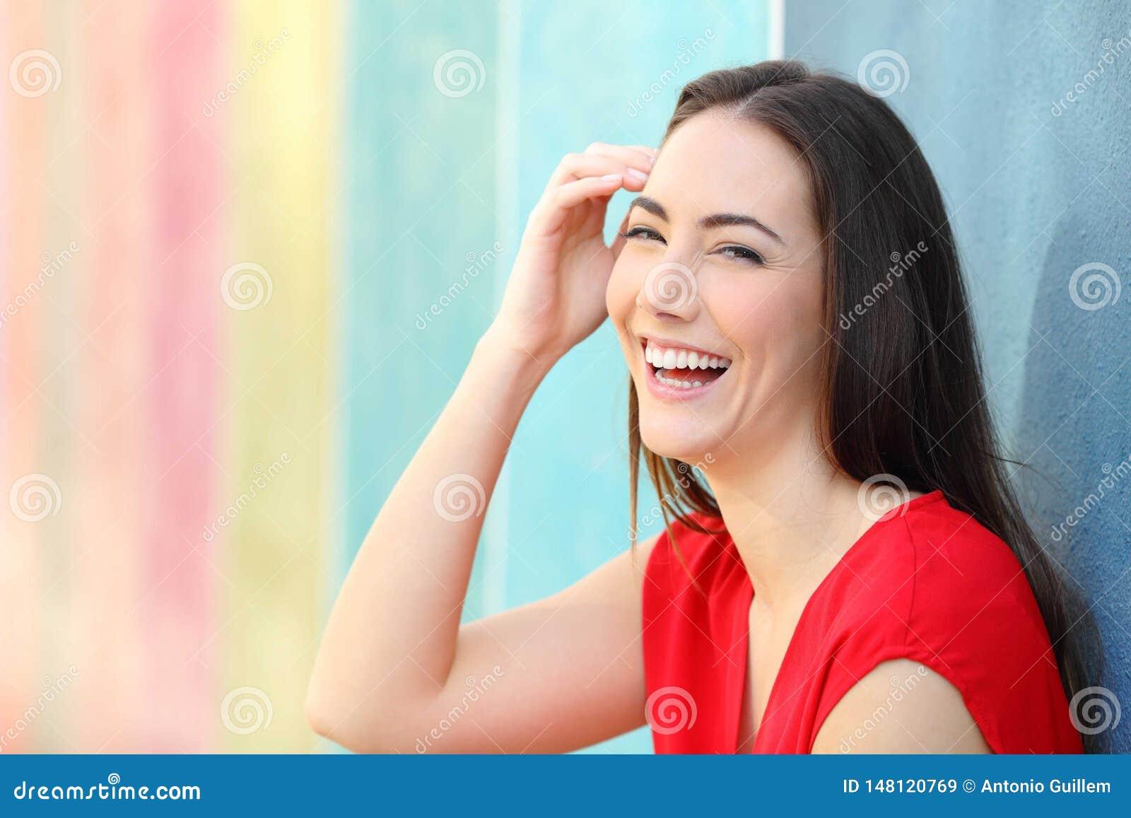 Femme joyeuse dans la caméra de regard riante rouge