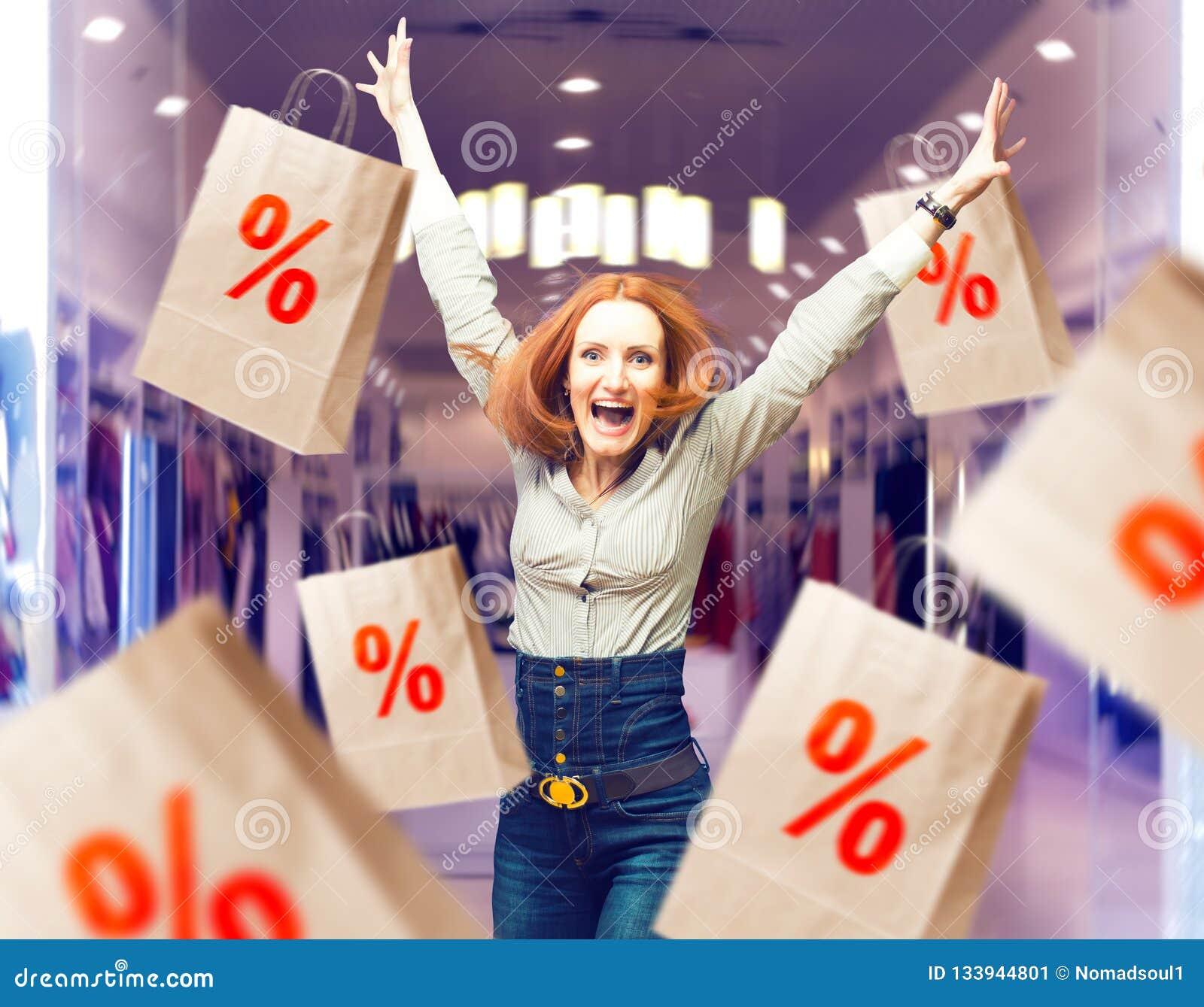 Femme joyeuse parmi des sacs en papier de vente dans le magasin