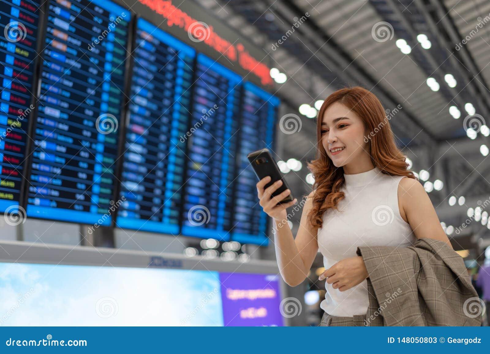 Femme ? l aide du smartphone avec le conseil de l information de vol ? l a?roport