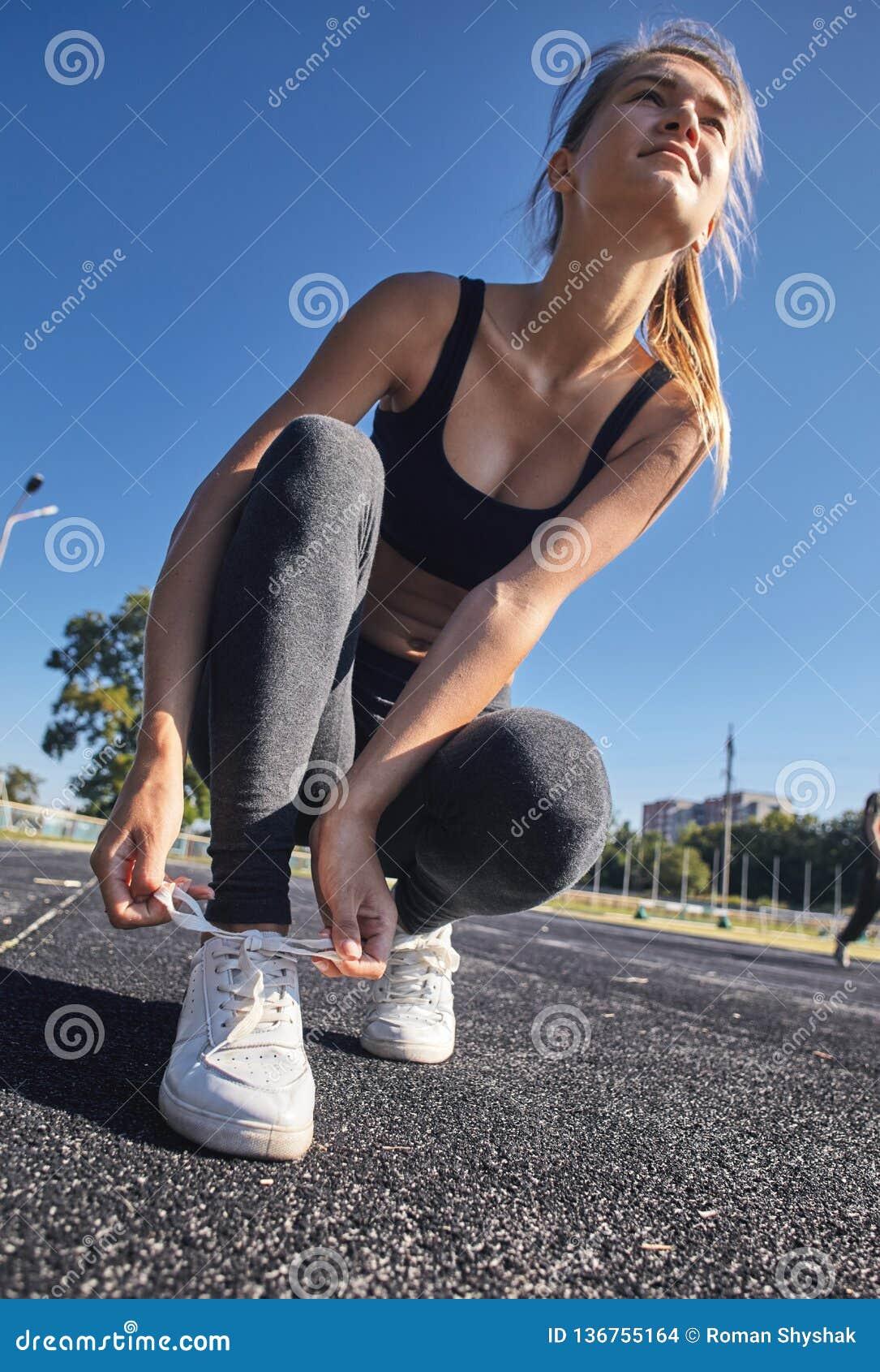 Femme laçant des chaussures de sport pour se préparer à la formation au lever de soleil