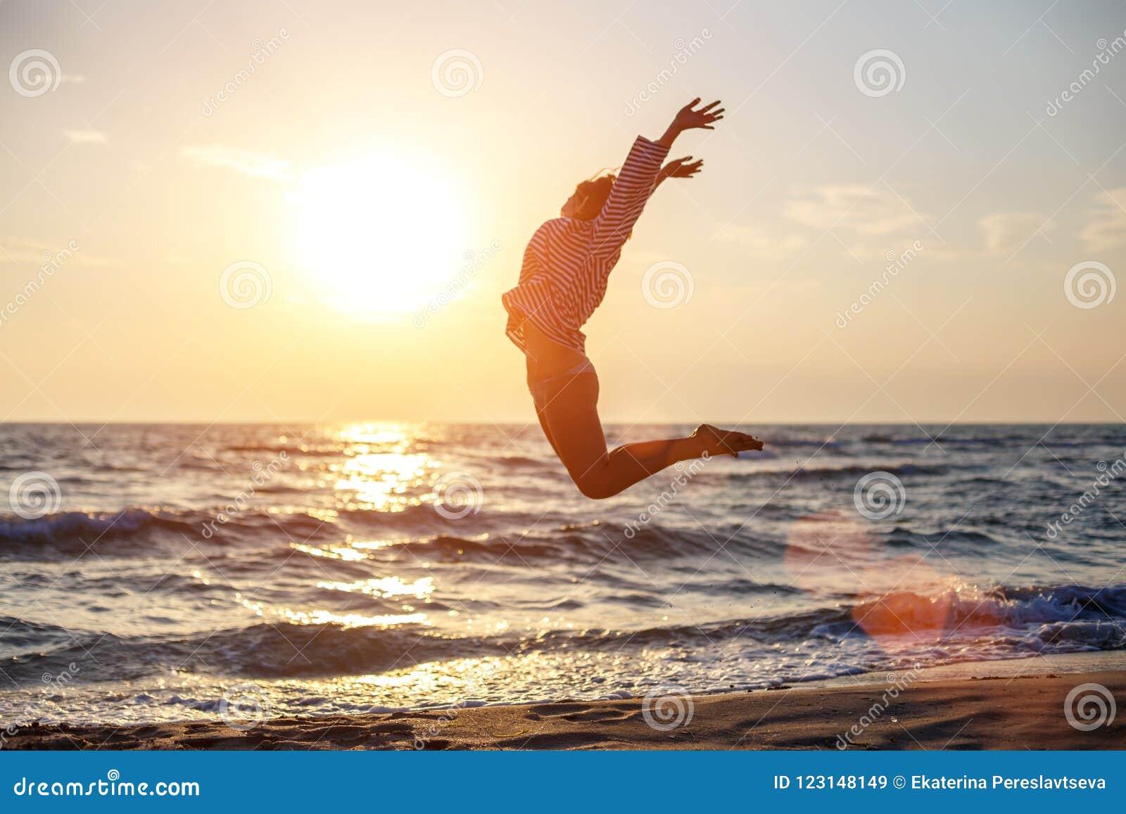 Femme libre heureuse sautant avec bonheur sur la plage dans le soleil de coucher du soleil