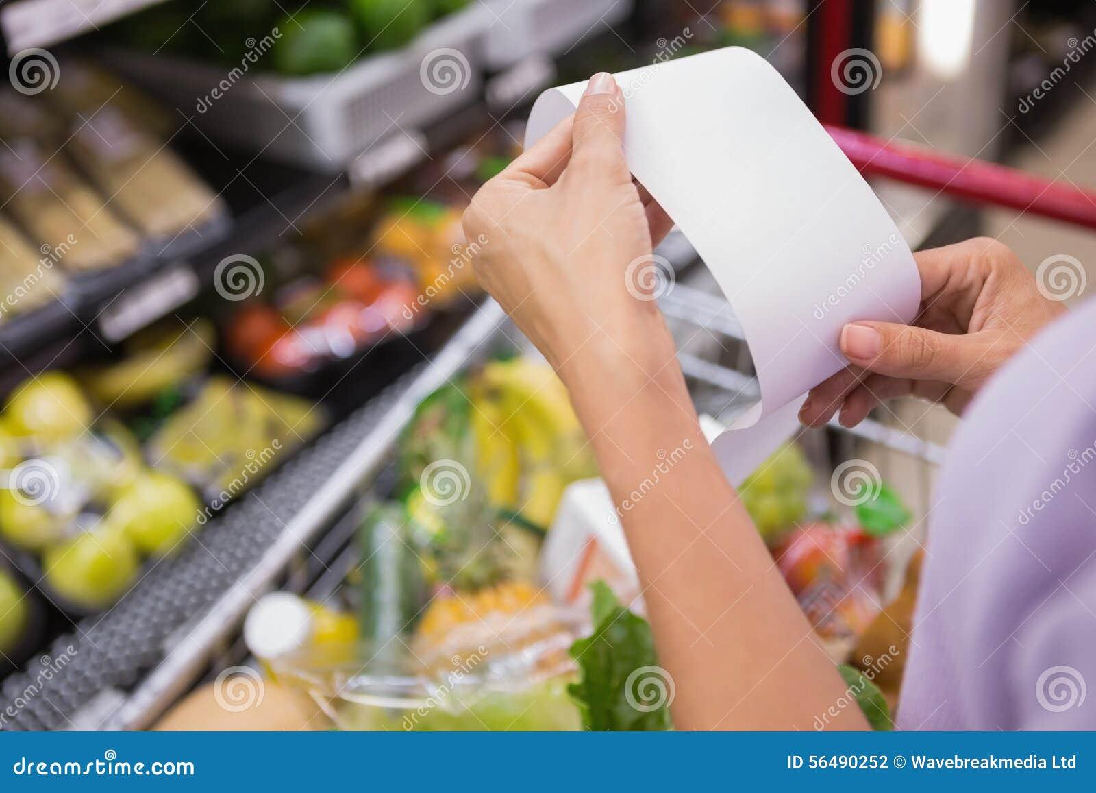 Femme lisant sa liste d achats