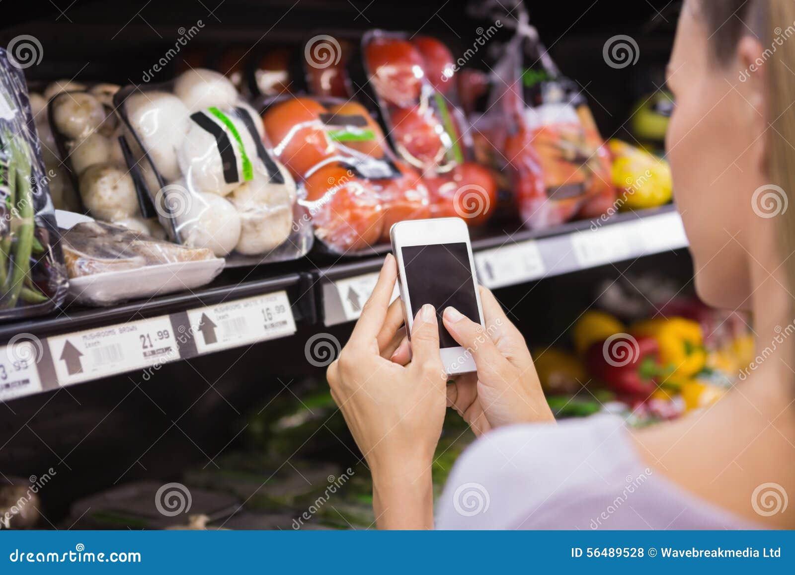 Femme lisant sa liste d achats sur le smartphone