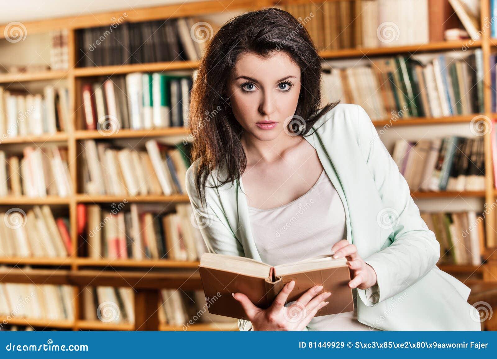 Femme lisant un livre devant des étagères
