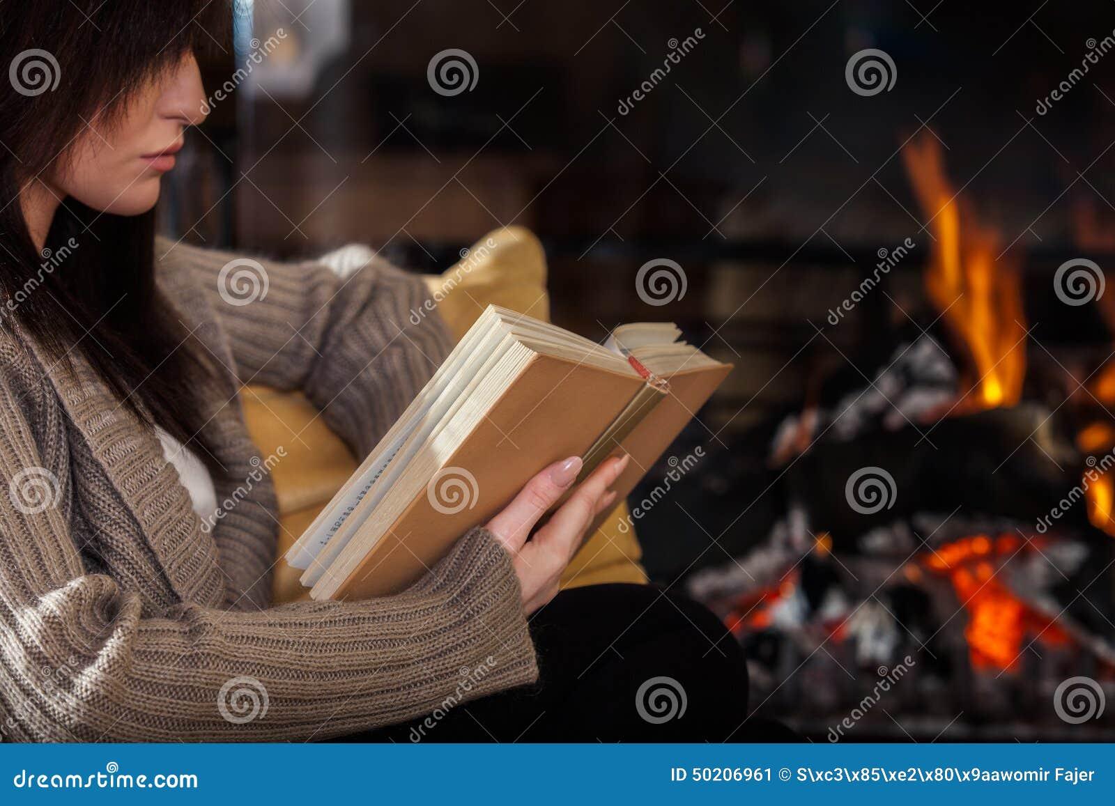Femme lisant un livre par la cheminée
