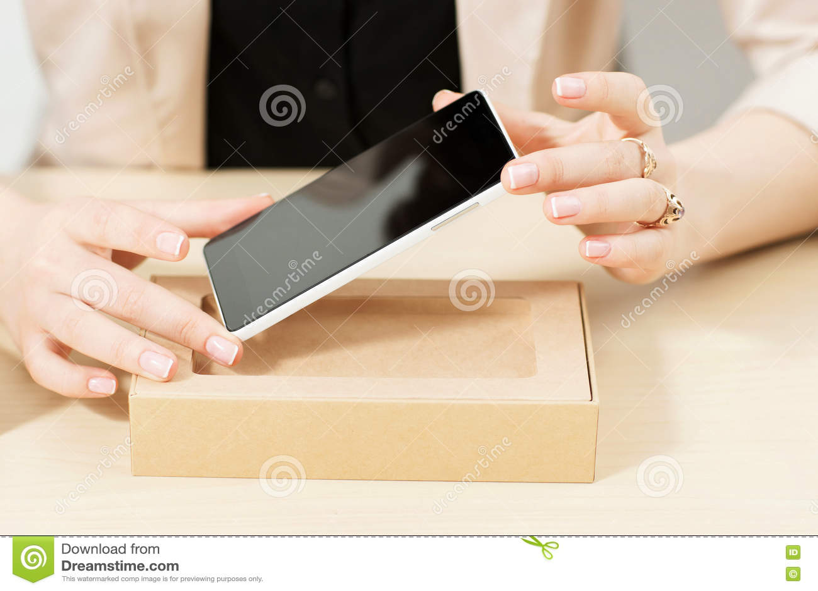 Femme méconnaissable obtenant le nouveau téléphone hors de la boîte