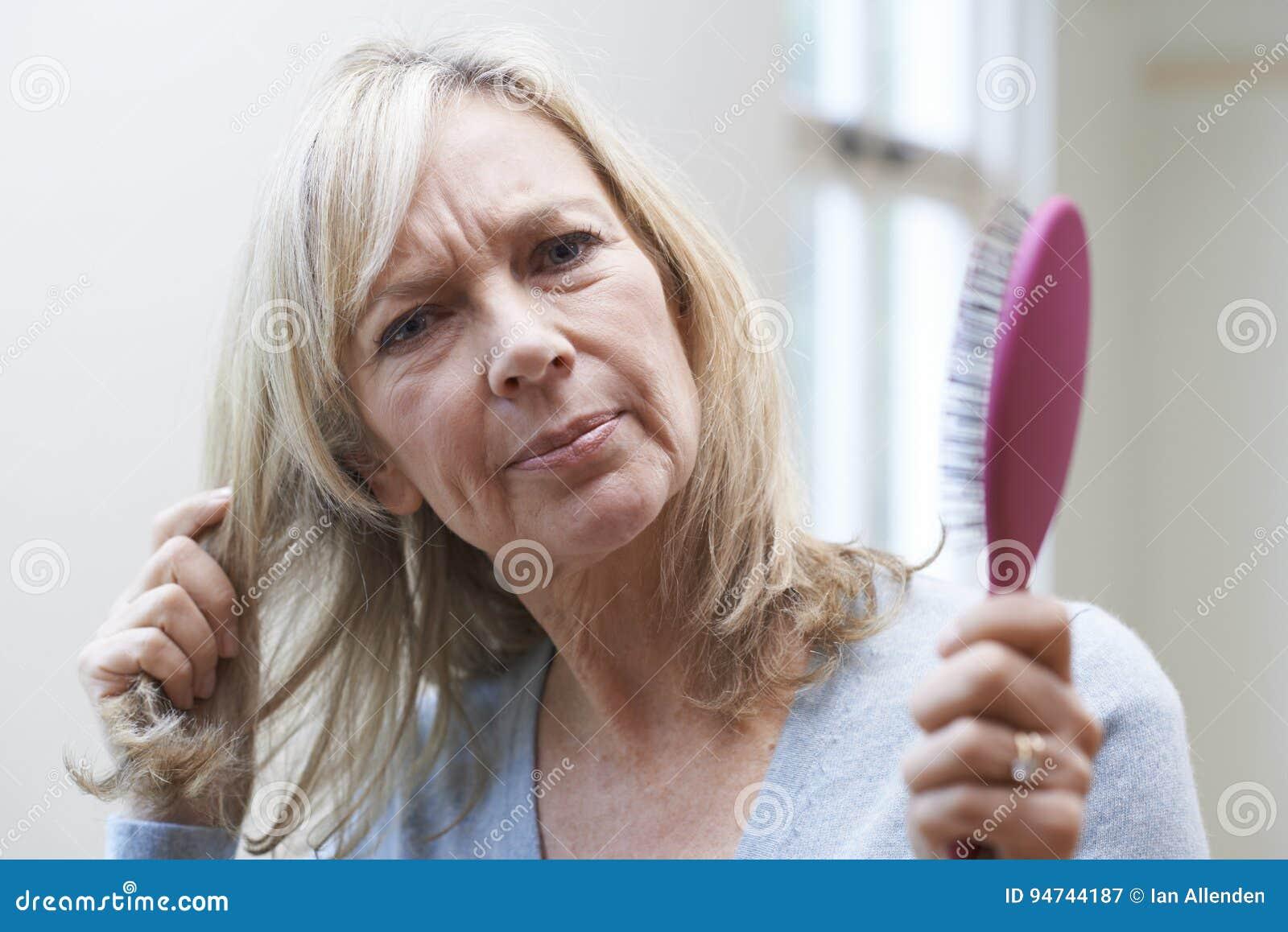 Femme mûre avec la brosse Corncerned au sujet de la perte des cheveux