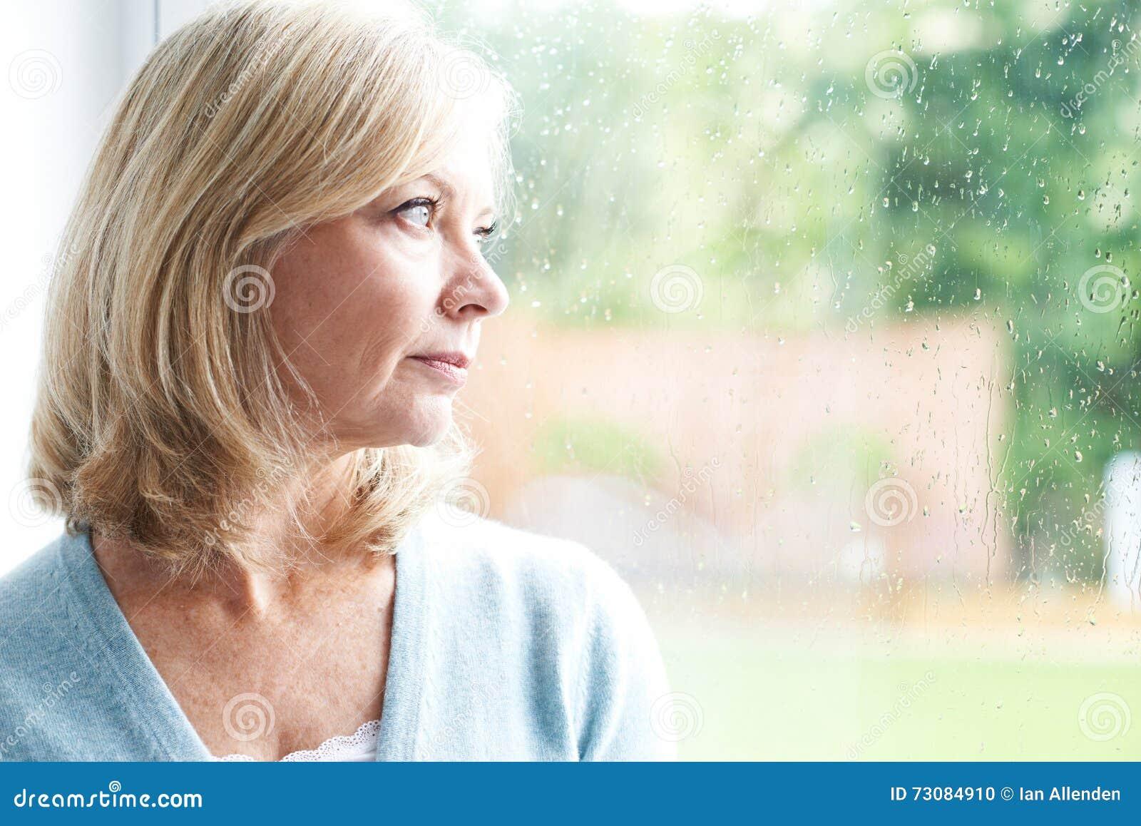 Femme mûre triste souffrant de l agoraphobie regardant hors de Windo