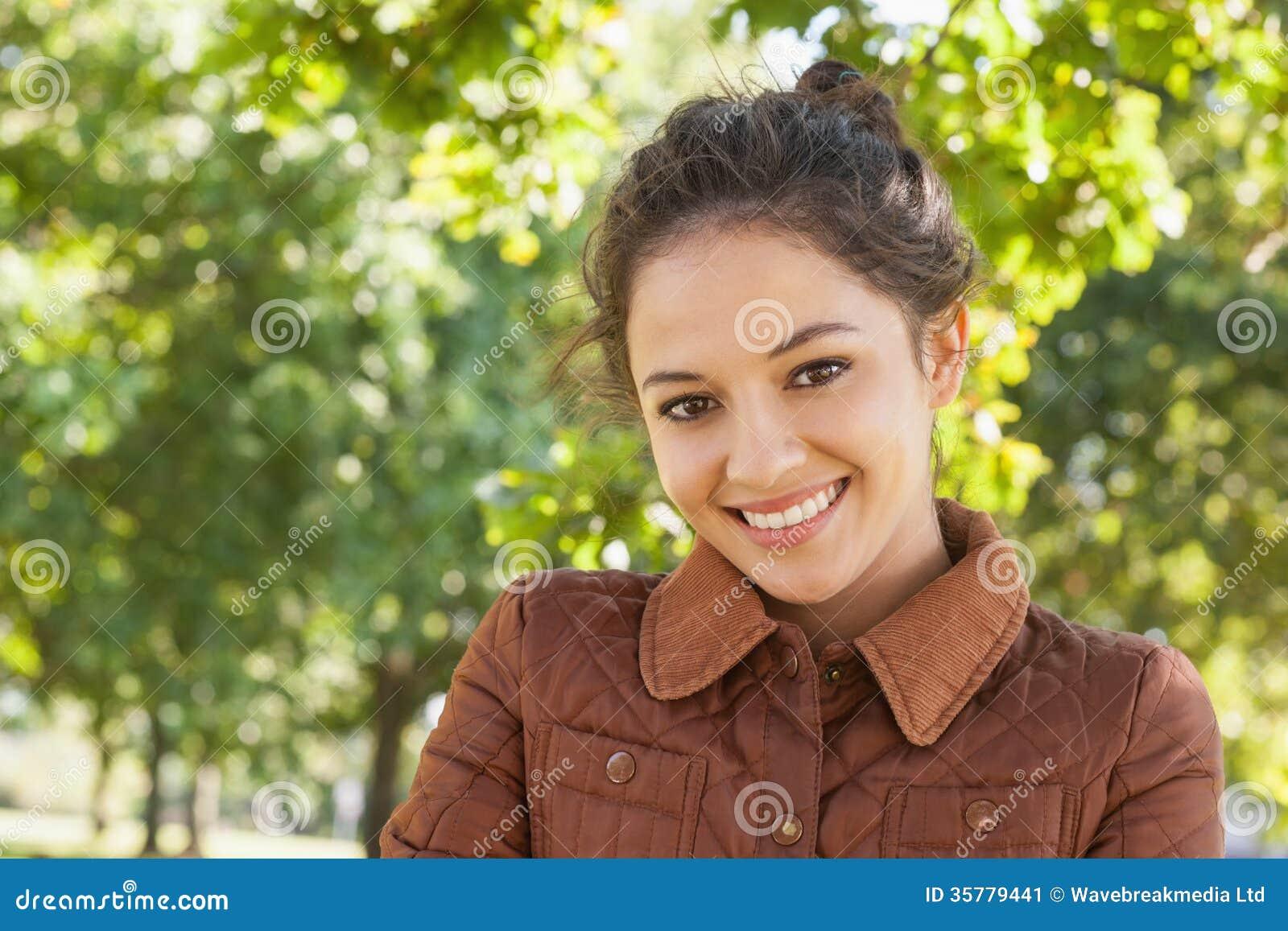Femme magnifique posant portant un manteau en parc