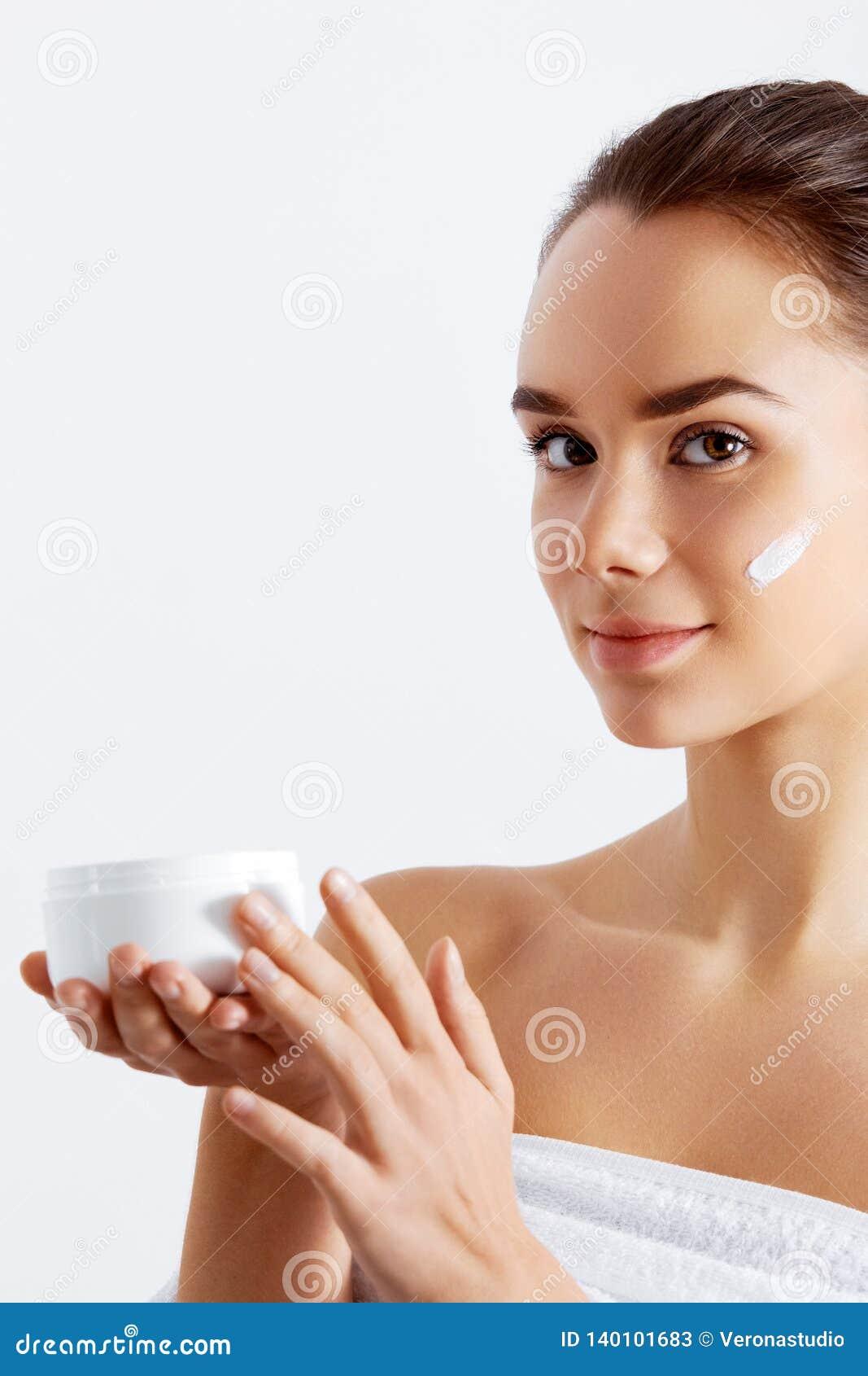 Femme magnifique tenant la crème de peau C est le meilleur produit cosmétique Tenant hydrater la lotion Concept de beauté