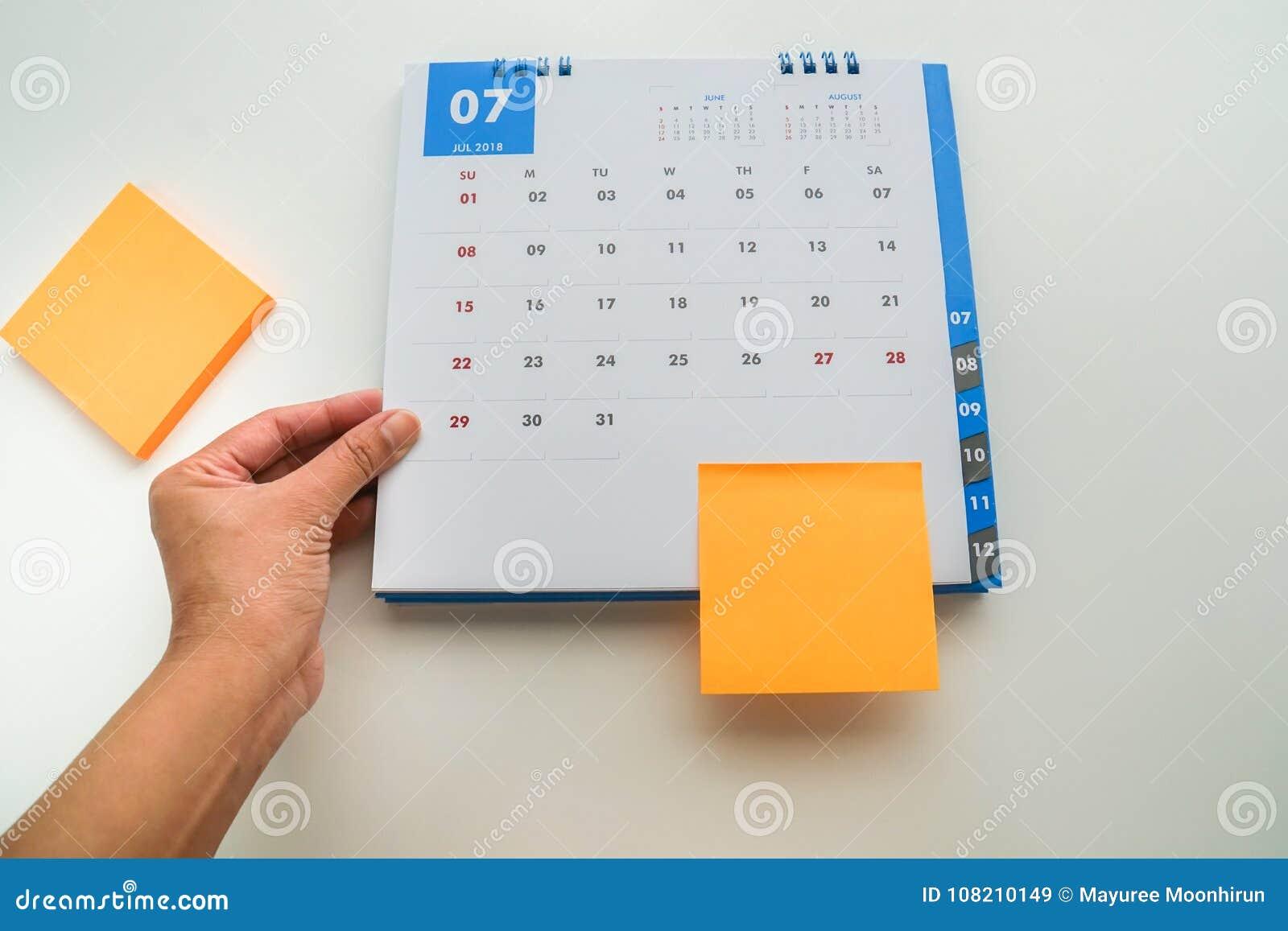 Femme main prise calendrier haut étroit d isolement en juillet 2018