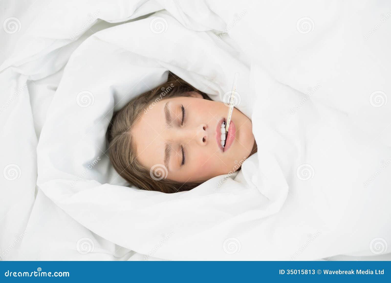 femme malade attirante se trouvant sous la couverture sur son lit image stock image 35015813. Black Bedroom Furniture Sets. Home Design Ideas