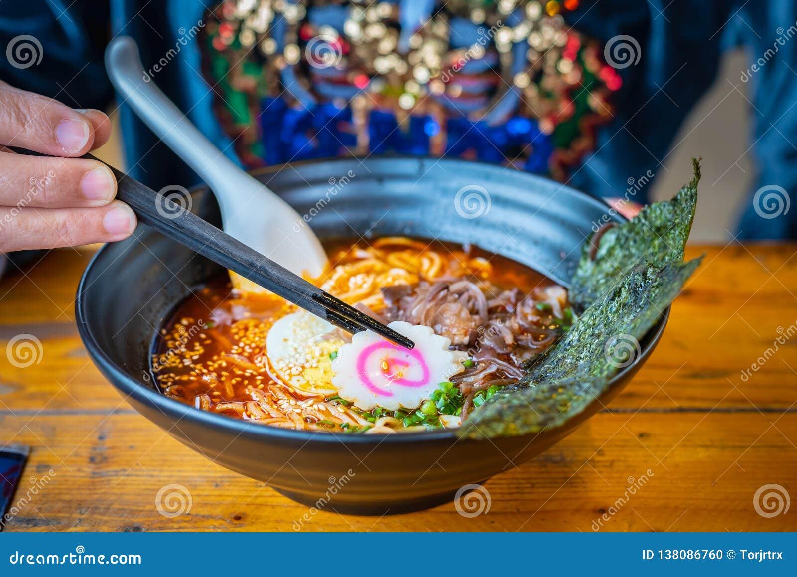 Femme mangeant d une soupe de nouilles japonaise de ramen épicés dans un bol noir de ramen de couleur