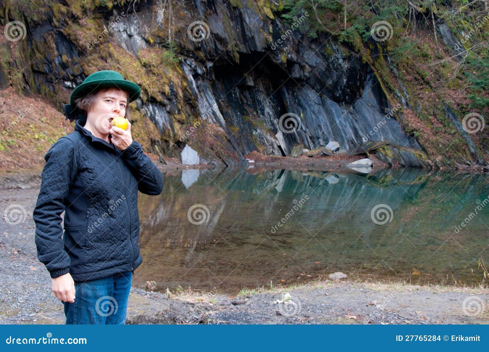 Femme mangeant la pomme par un regroupement de montagne