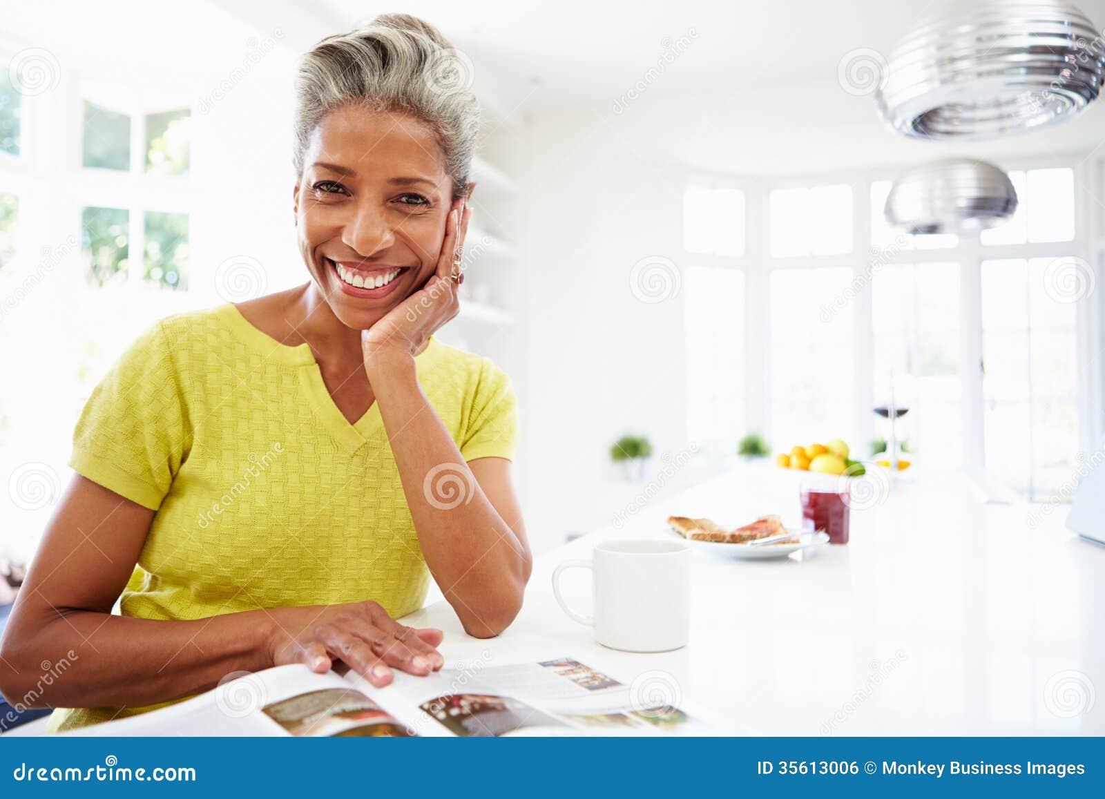 Femme mangeant le petit déjeuner et lisant le magazine