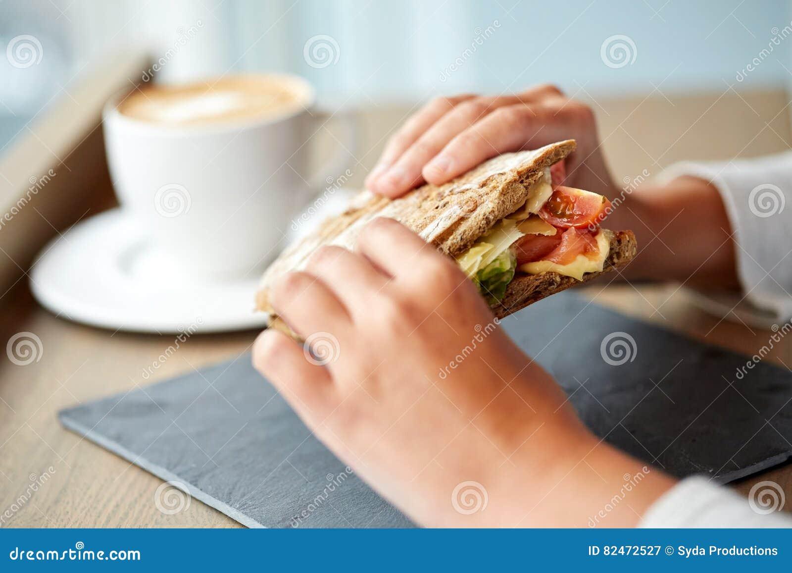 Femme mangeant le sandwich saumoné à panini au restaurant