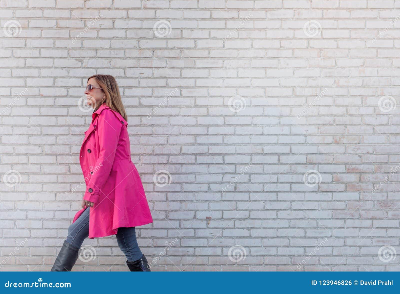 Femme marchant contre le mur de briques - surexposé pour l effet