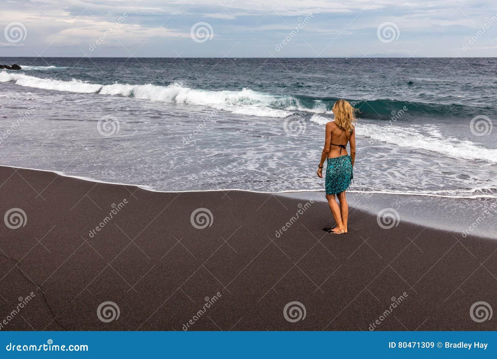 femme marchant le long de la plage noire de sable dans padangbai le de bali indon sie image. Black Bedroom Furniture Sets. Home Design Ideas
