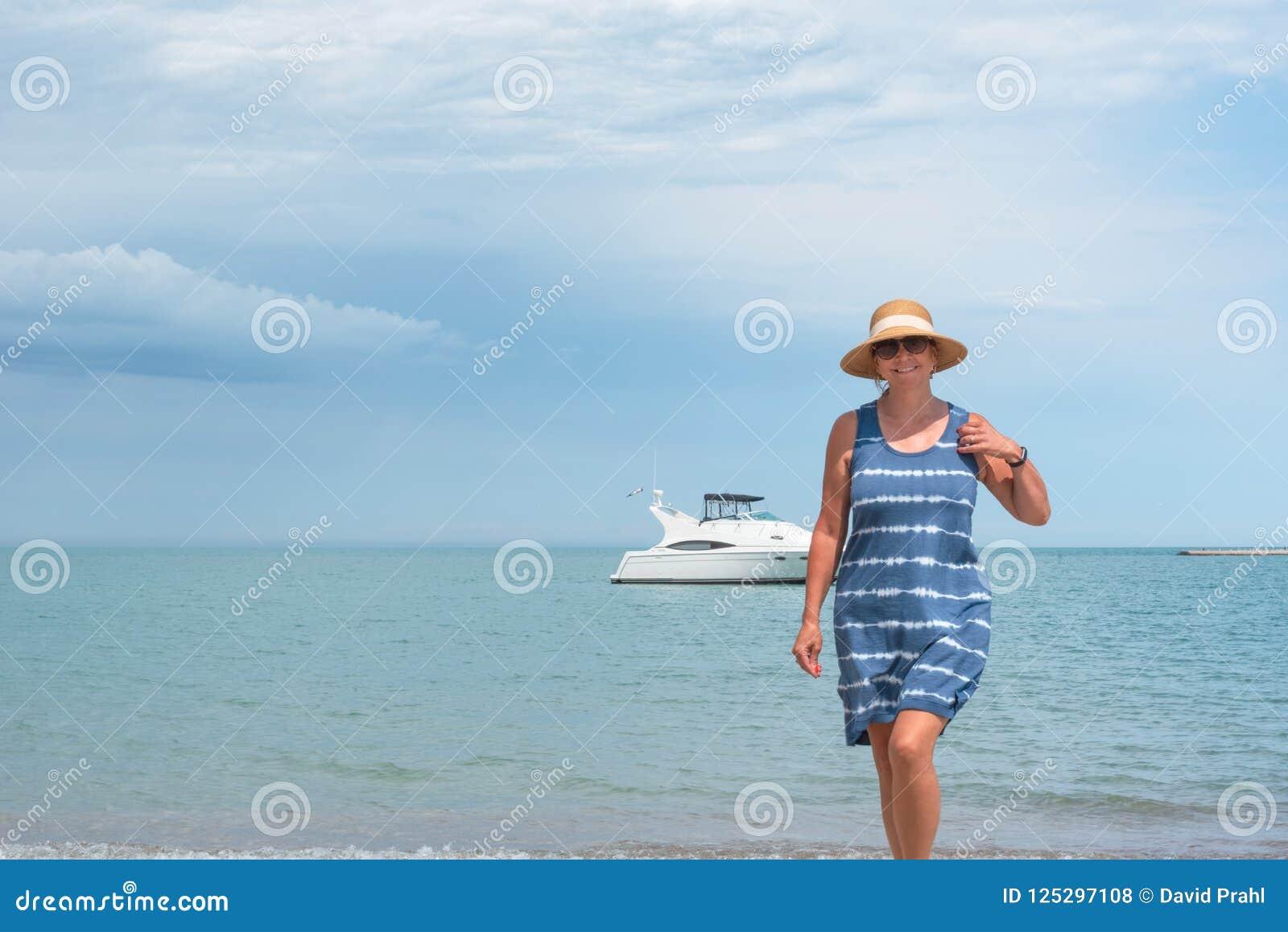 Femme marchant sur la plage avec le yacht à l arrière-plan