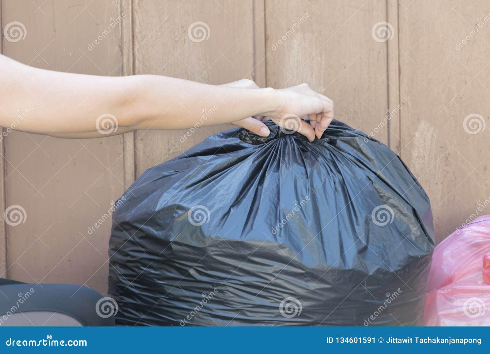 Femme mettant le sac de déchets dans la poubelle Liez-le pour le rendre facile à se déplacer