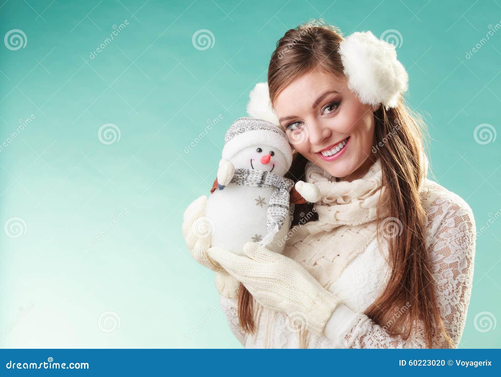 Femme mignonne de sourire avec le petit bonhomme de neige L hiver