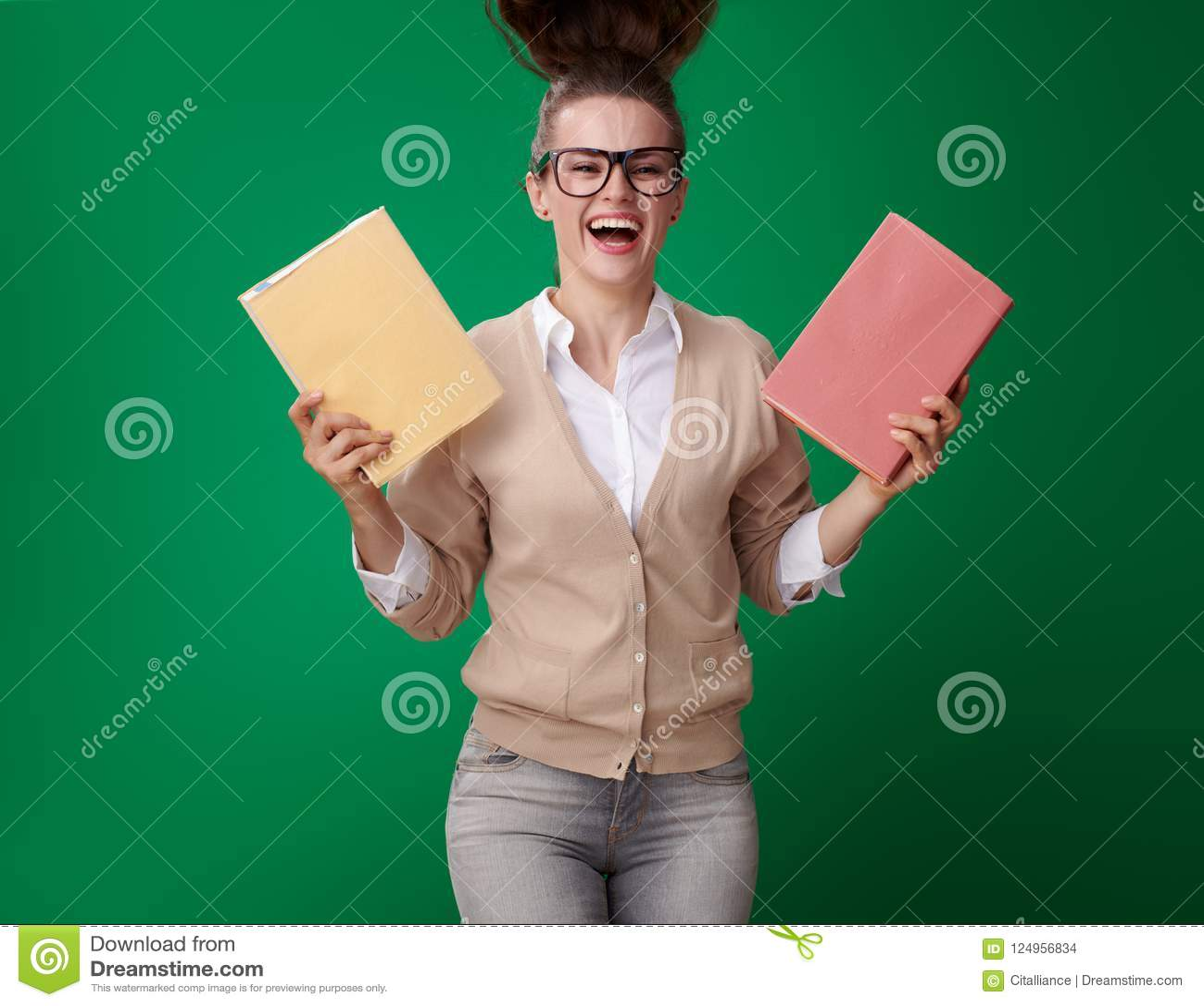 Femme moderne active d étudiant avec des livres sur le fond vert