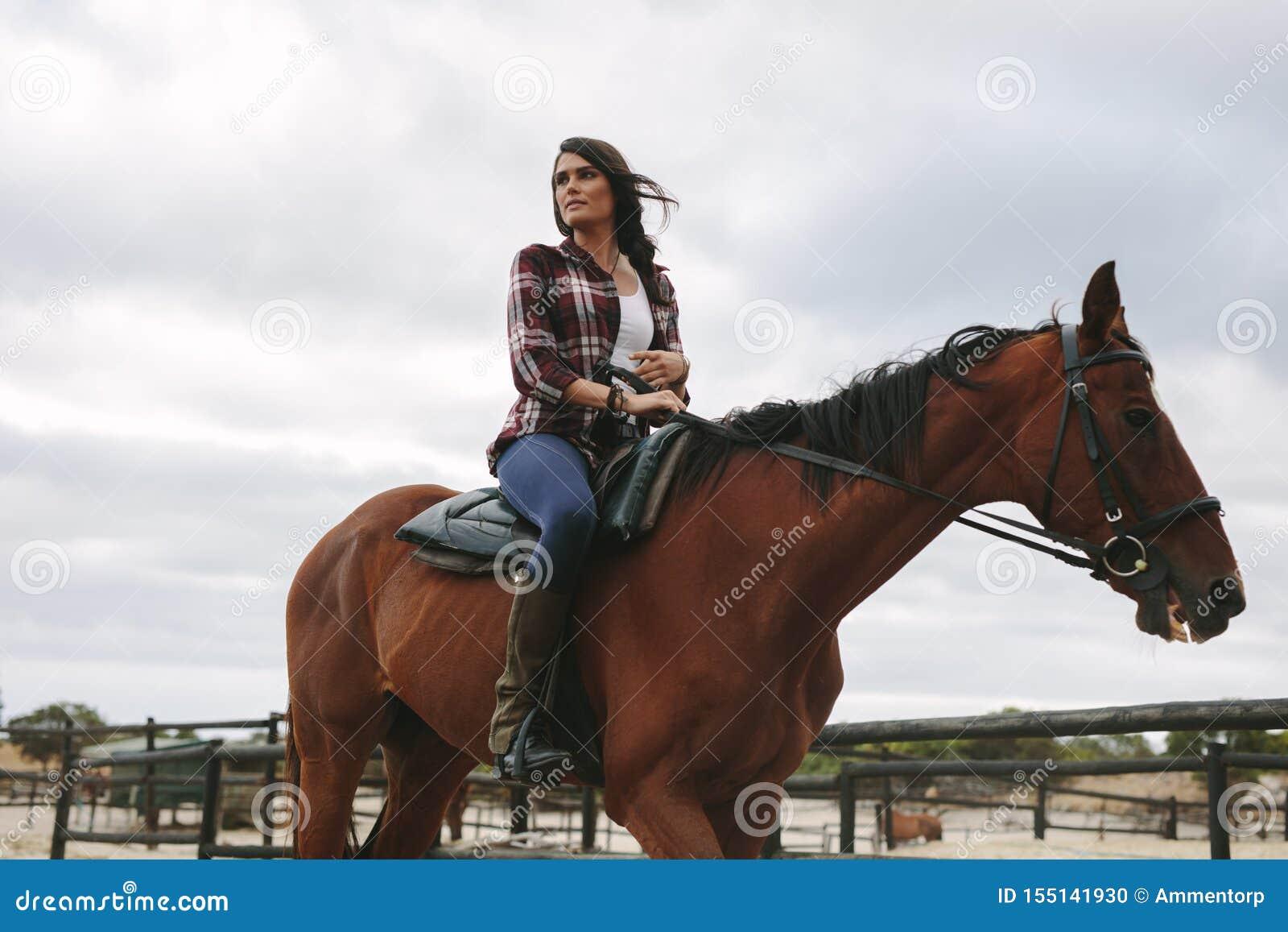 Femme montant son cheval dans le corral