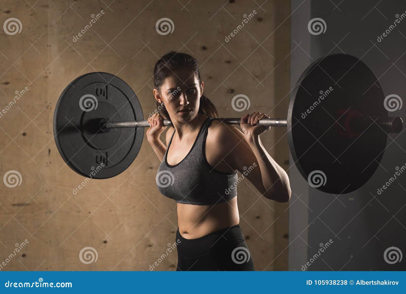 Femme musculaire dans un gymnase faisant des exercices lourds avec le barbell