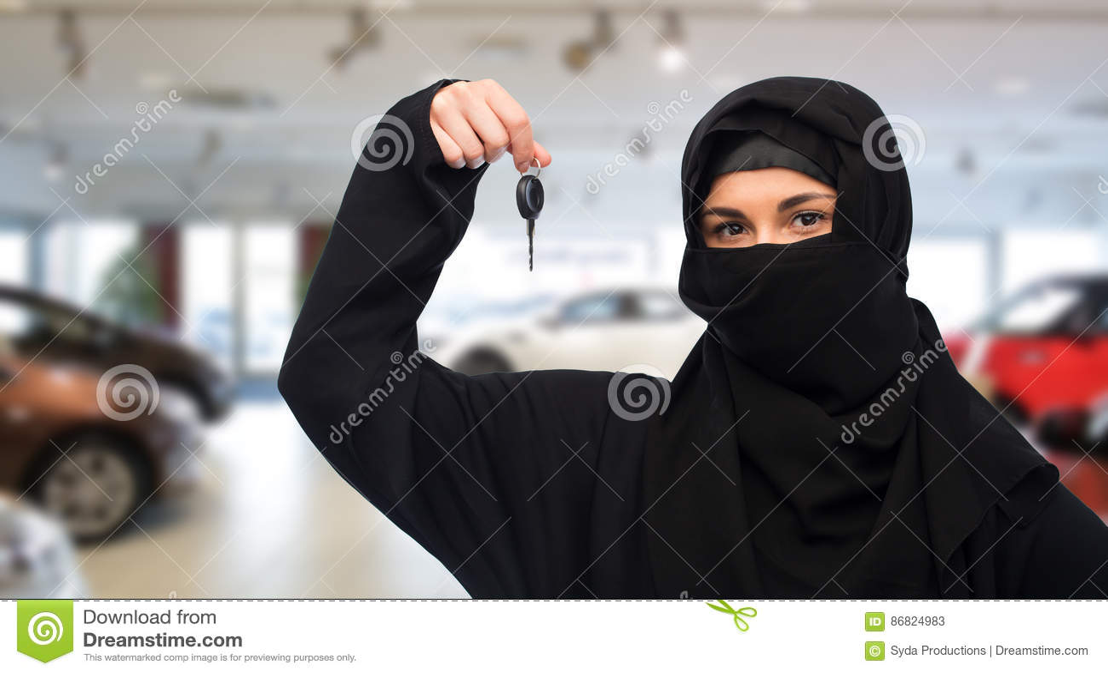 Femme musulmane dans le hijab avec la clé de voiture au-dessus du salon automobile
