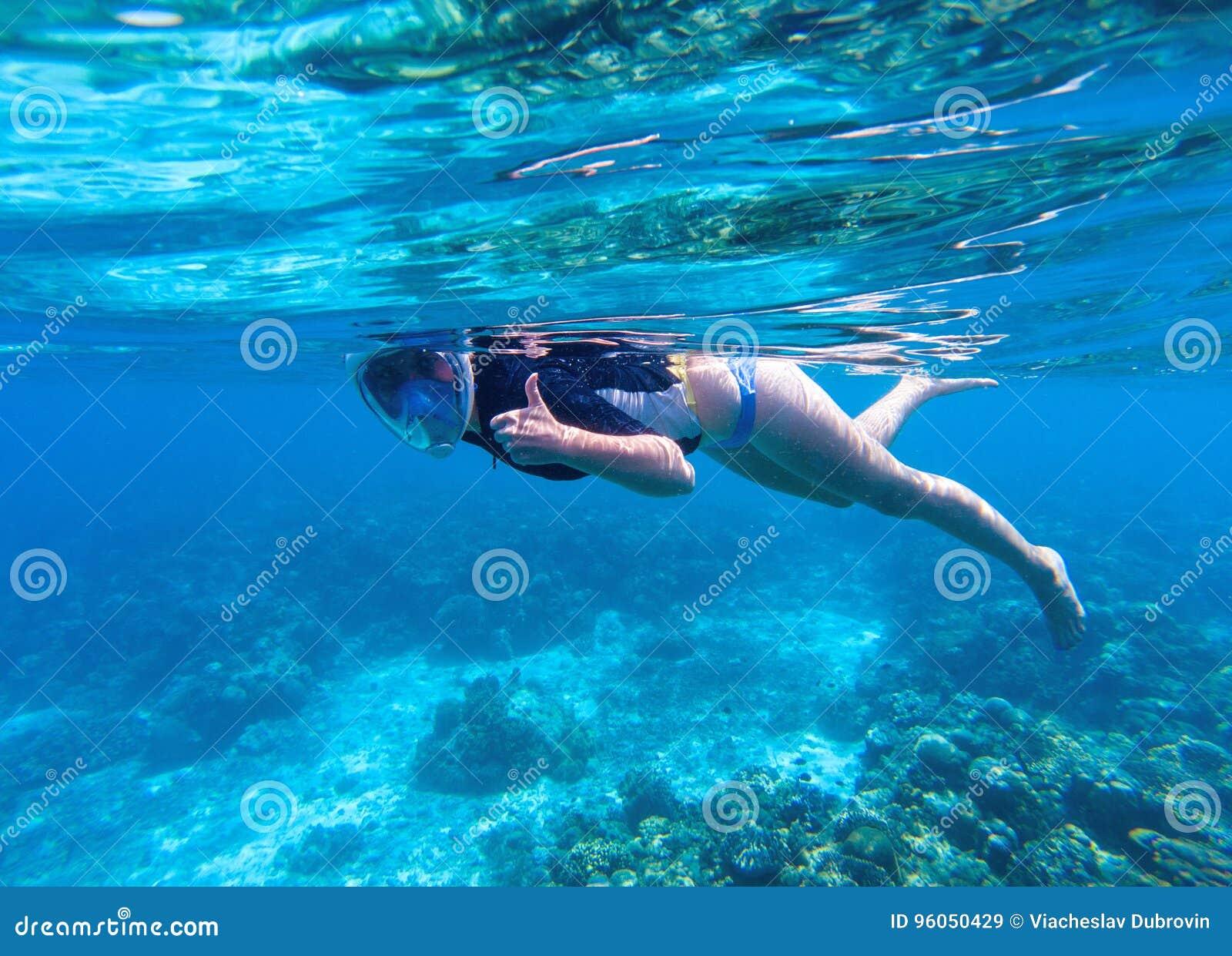 Femme naviguant au schnorchel dans l eau bleue La prise d air montre le pouce dans le plein masque protecteur