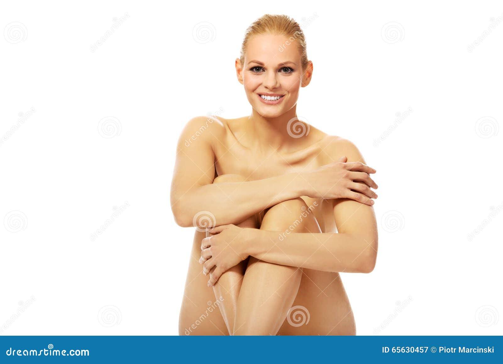 Femme nue de sourire s asseyant sur le plancher