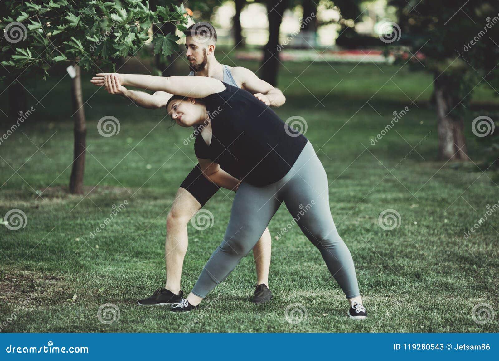 Femme obèse faisant étirant l exercice avec l entraîneur