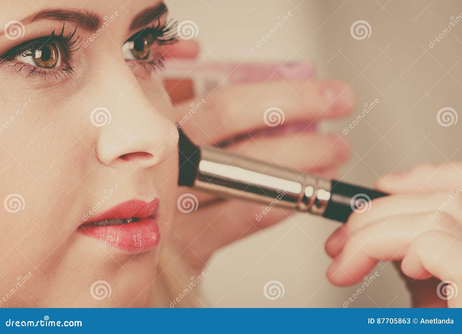 Femme obtenant lui le maquillage fait avec la brosse professionnelle