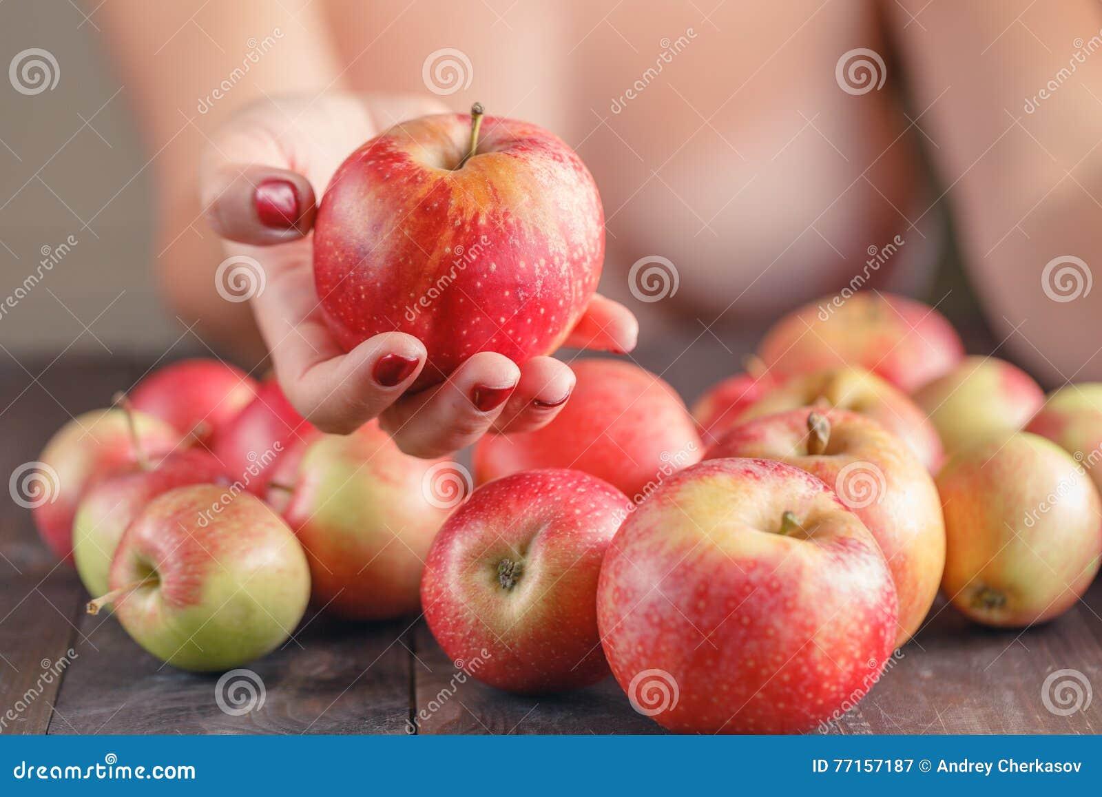 Femme offrant la pomme rouge, DOF peu profond, foyer sur la pomme