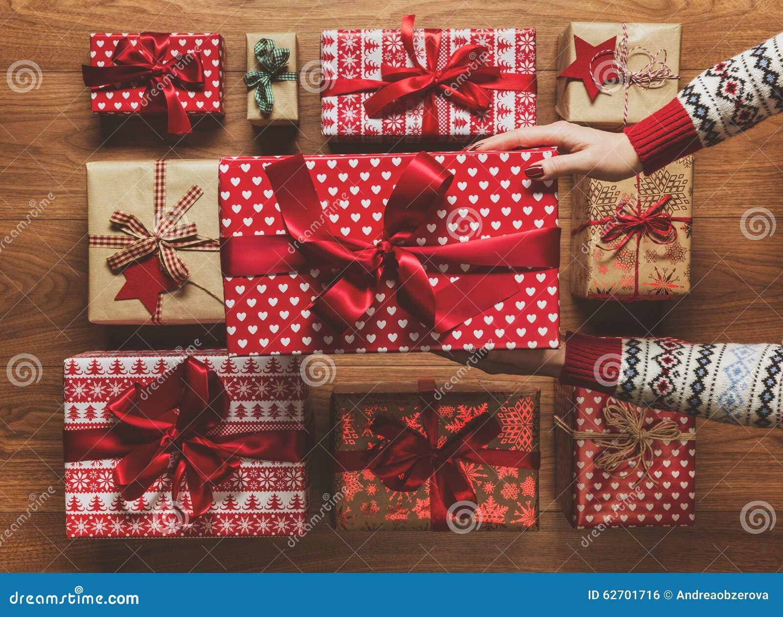 Femme organisant les cadeaux de Noël admirablement enveloppés de vintage sur le fond en bois, image avec la brume