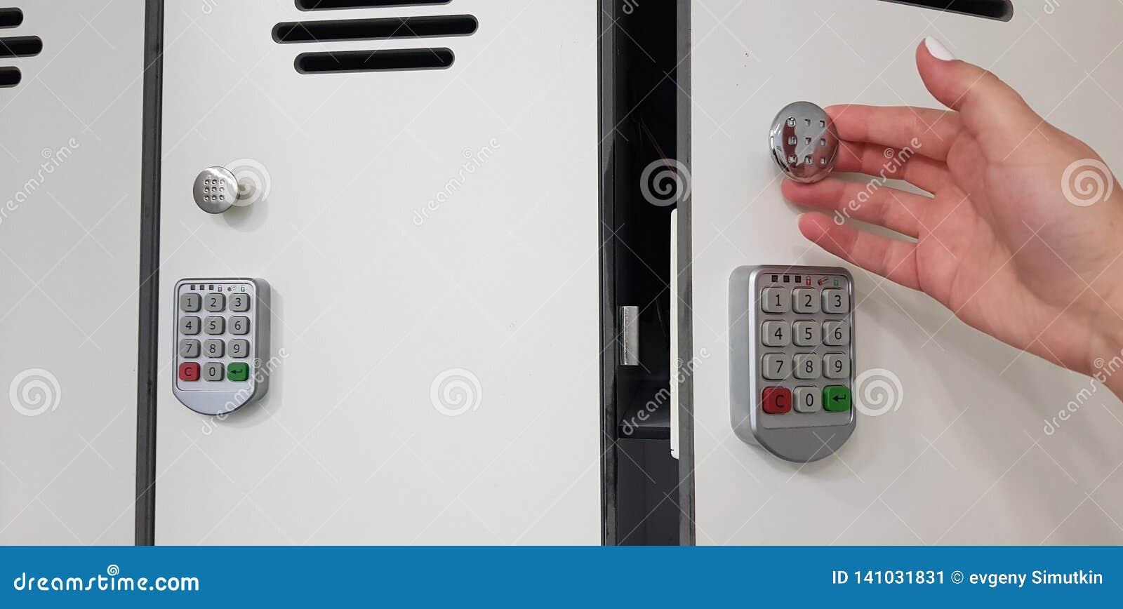 Femme ouvrant une porte du casier blanc de sécurité avec les serrures électriques de code