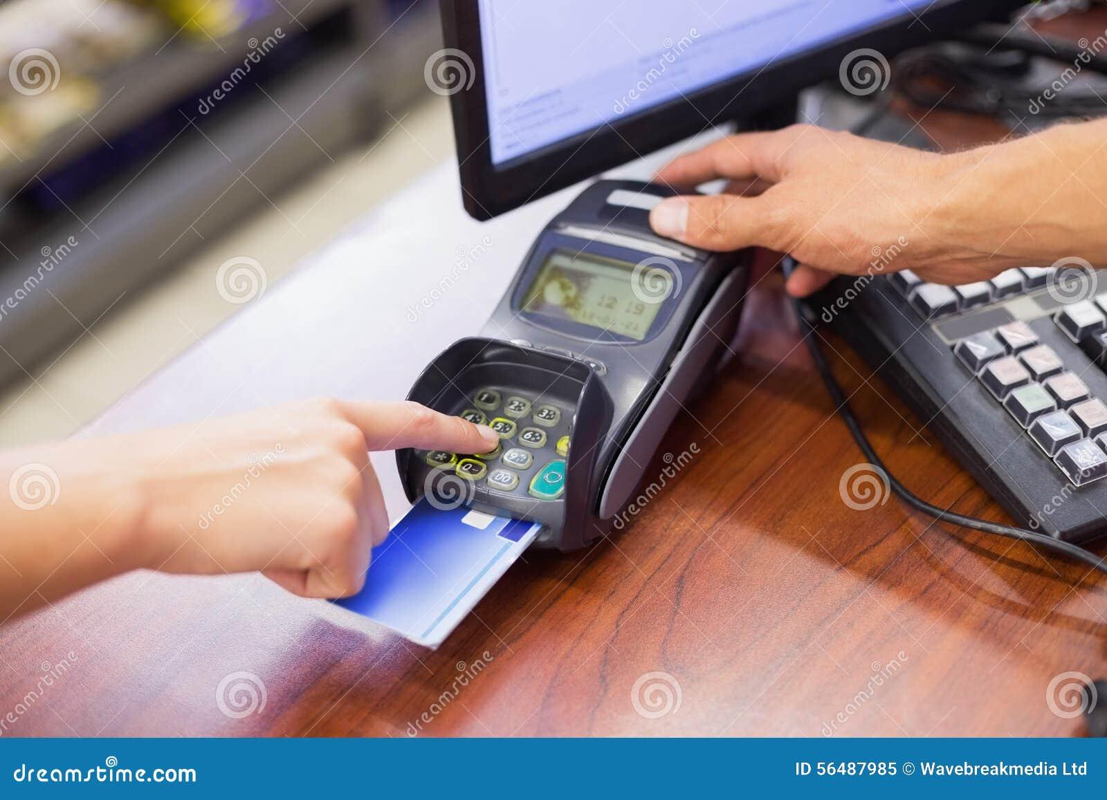 Femme payant avec sa carte de crédit et faisant son code de goupille
