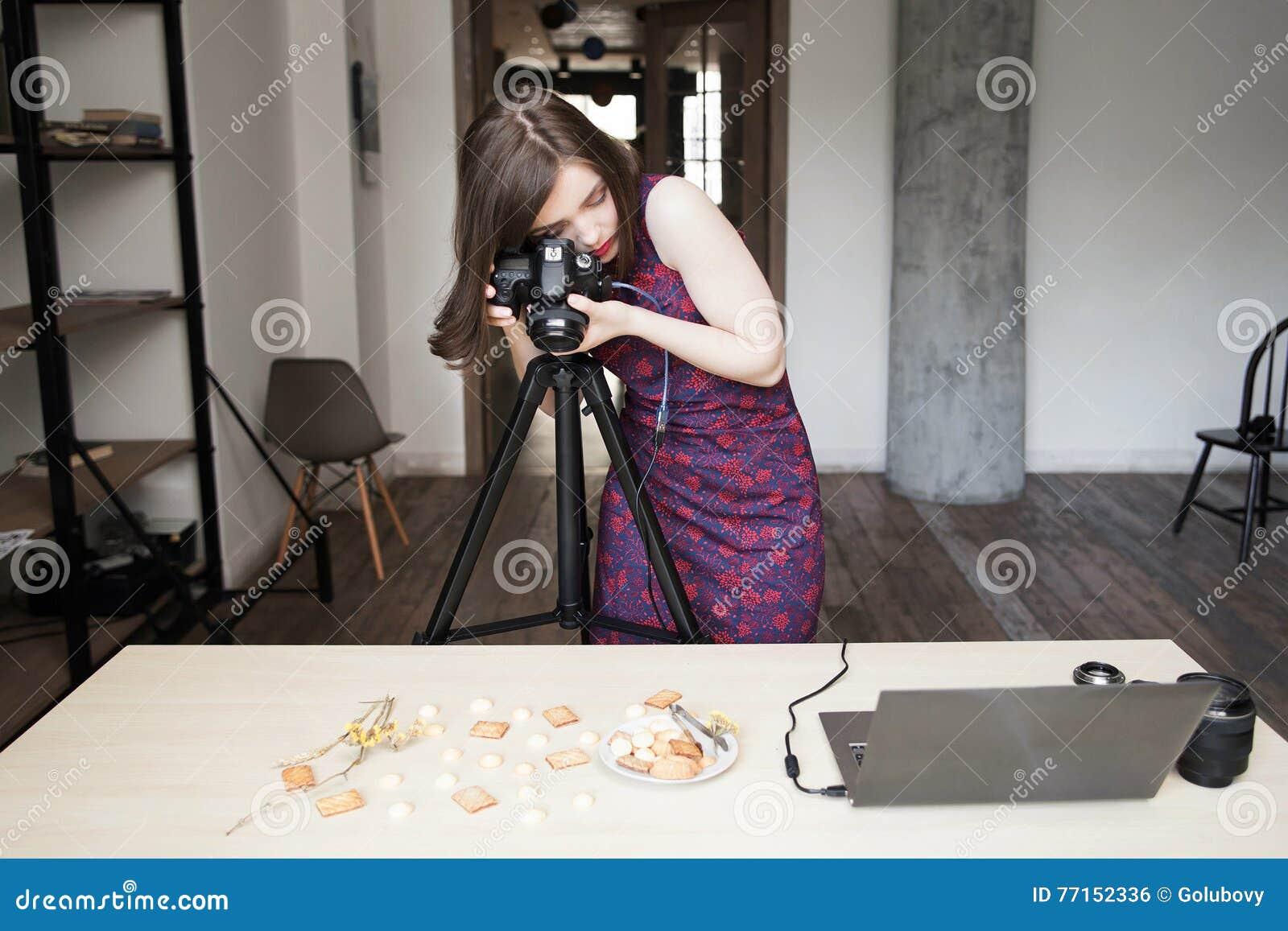 Femme photographiant des biscuits réglés dans le studio