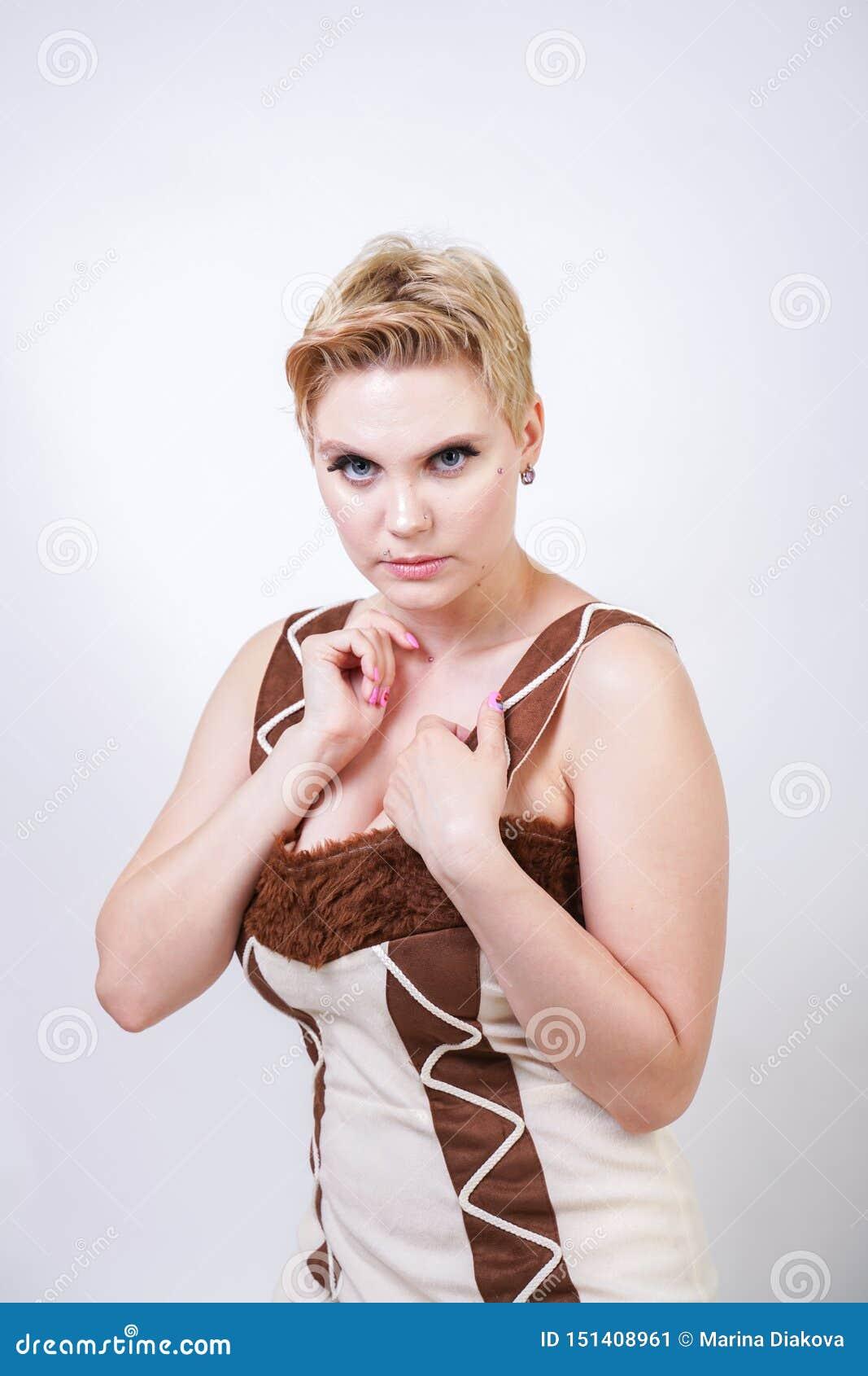 Femme plus chaude de taille dans le costume de carnaval de fourrure de l homme primitif sur le fond blanc dans le studio une bell